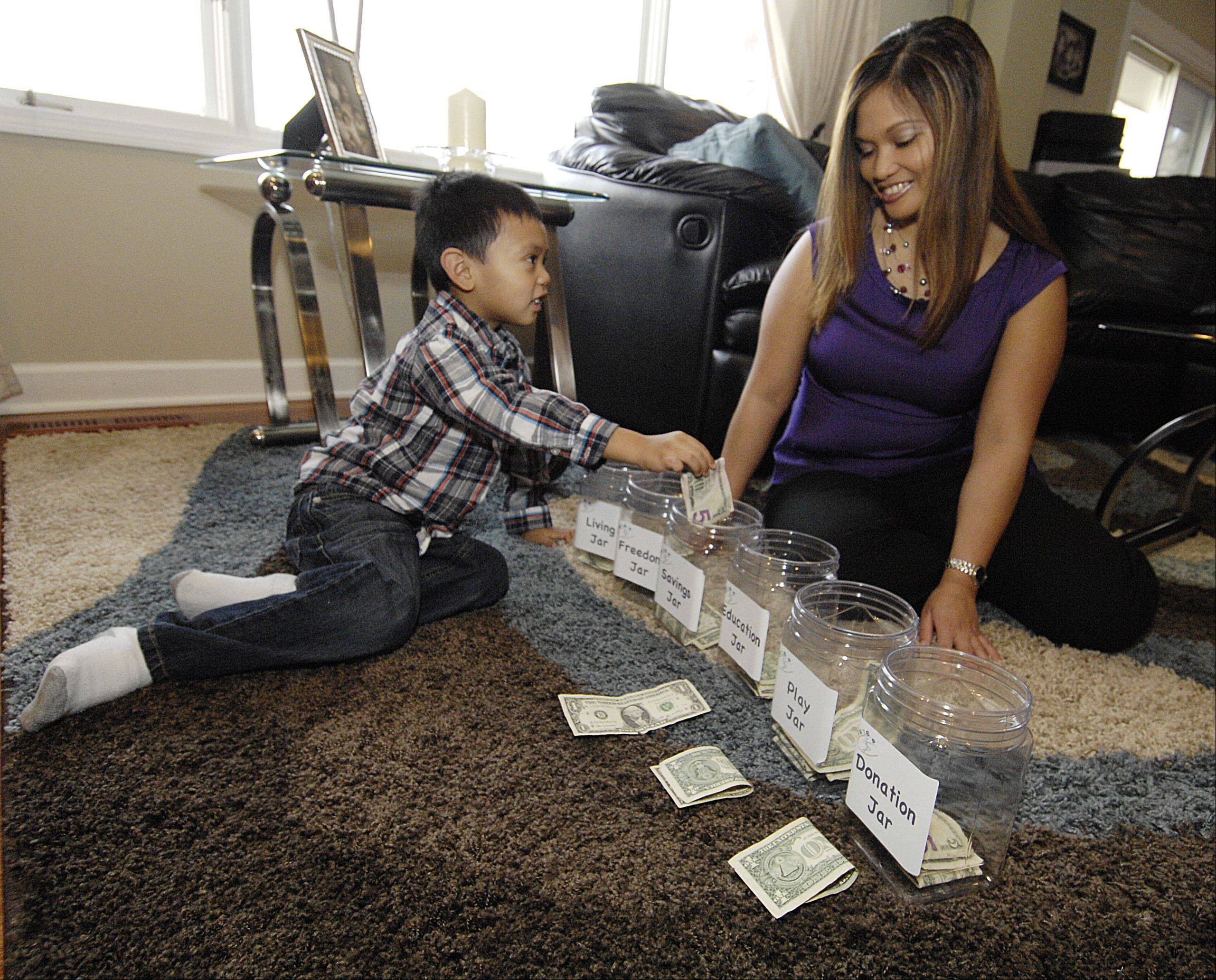 Dean Javier, 4, places money in labeled money jars to help him organize his money, while his mother Melanie Jane Nicolas looks on. Fifty percent of gifts and allowance money go into the living jar for wants and needs. The rest is divided equally among the jars for financial freedom (investments), savings, education, play and donations.