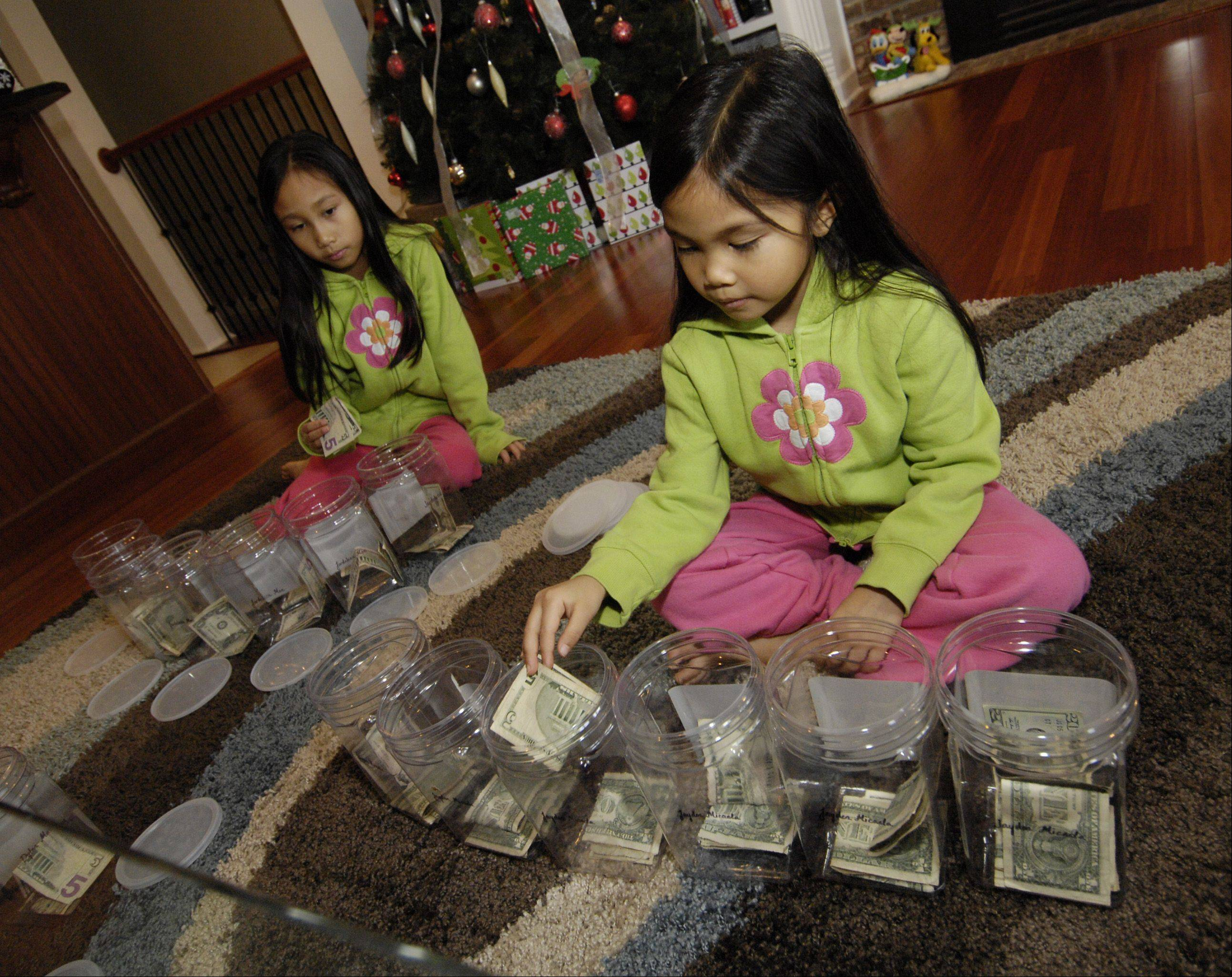Jardeleza Javier, 9, and her sister Jayden, 5, put money in their labeled money jars. Their mother, Melanie Jane Nicolas, believes kids should start to manage their own money as soon as they understand the difference between a want and a need.