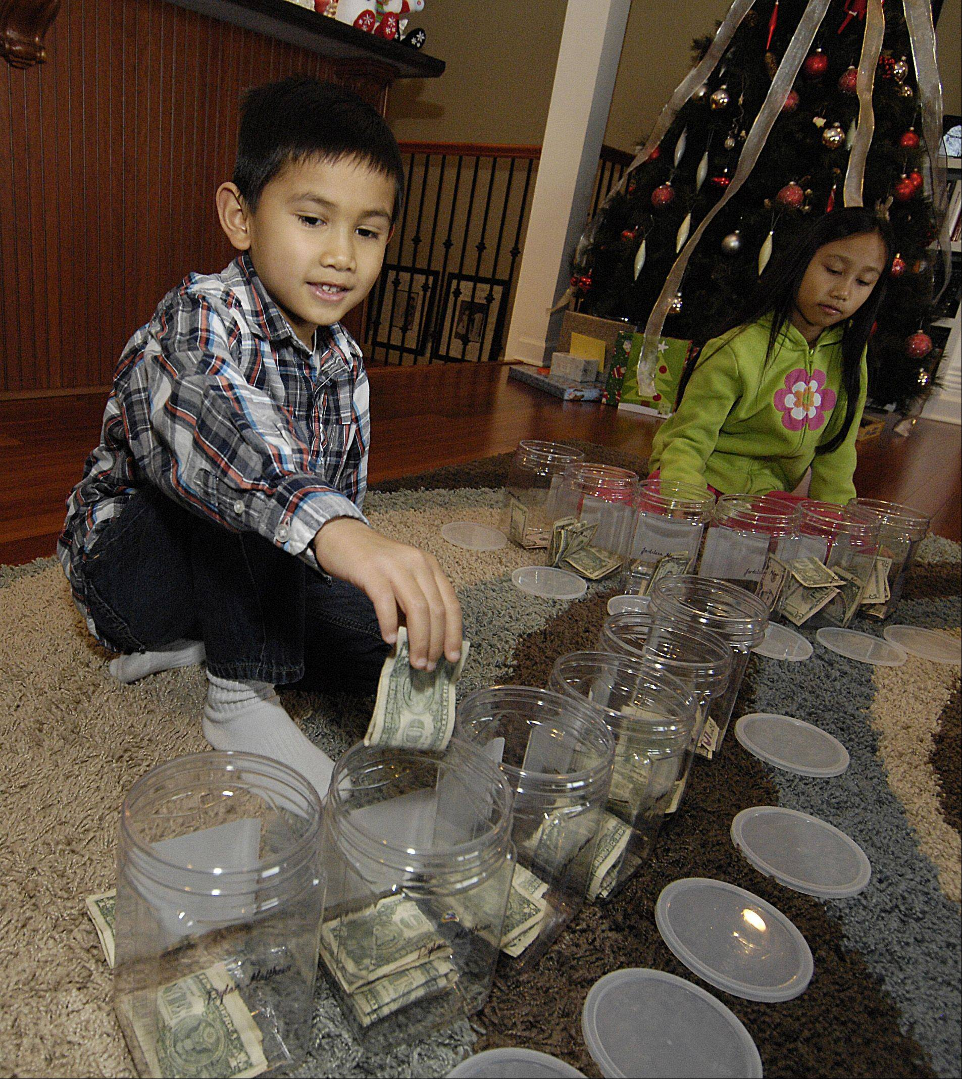 Dylan Javier, 6, and his sister Jardeleza, 9, divide their money among their money jars. The children do extra chores to earn more money.