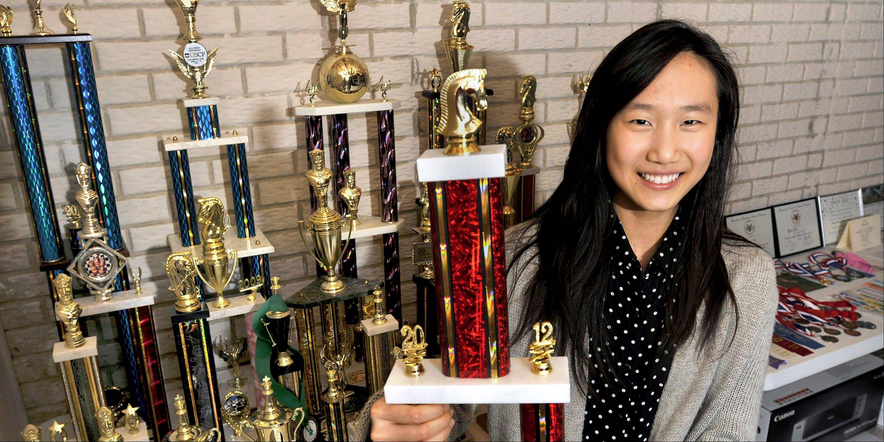 "Urbana High School sophomore Yue ""Penny"" Xu, 16, surrounded by a table full of chess trophies, at her home in Urbana."