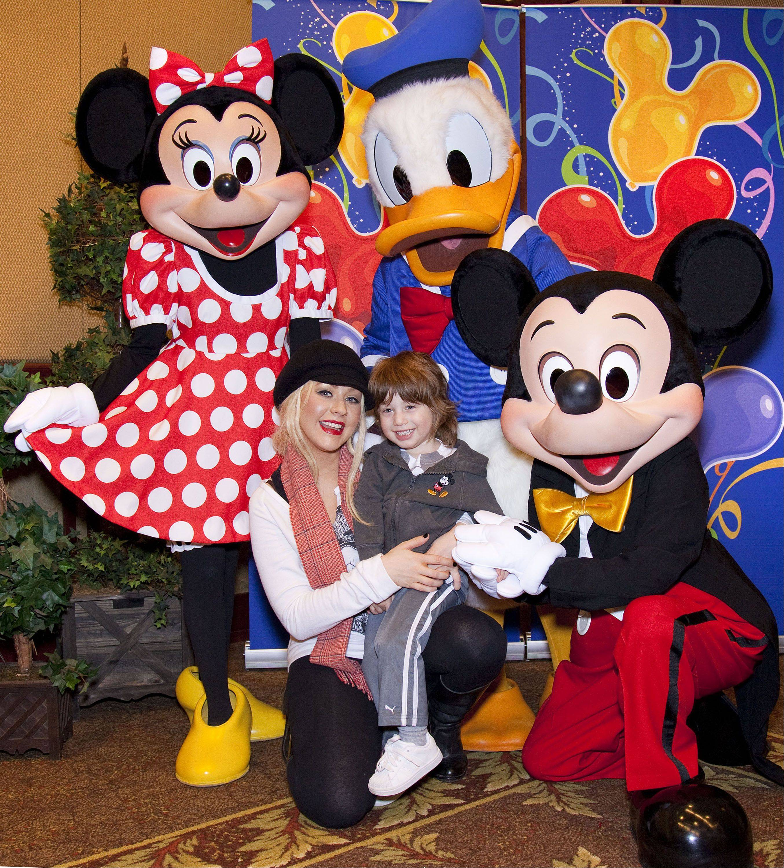 Mickey Mouse and Donald Duck wear their trademark bow ties for this 2011 photo with singer Christina Aguilera and her son Max. Minnie Mouse opts to wear her bow in her hair.