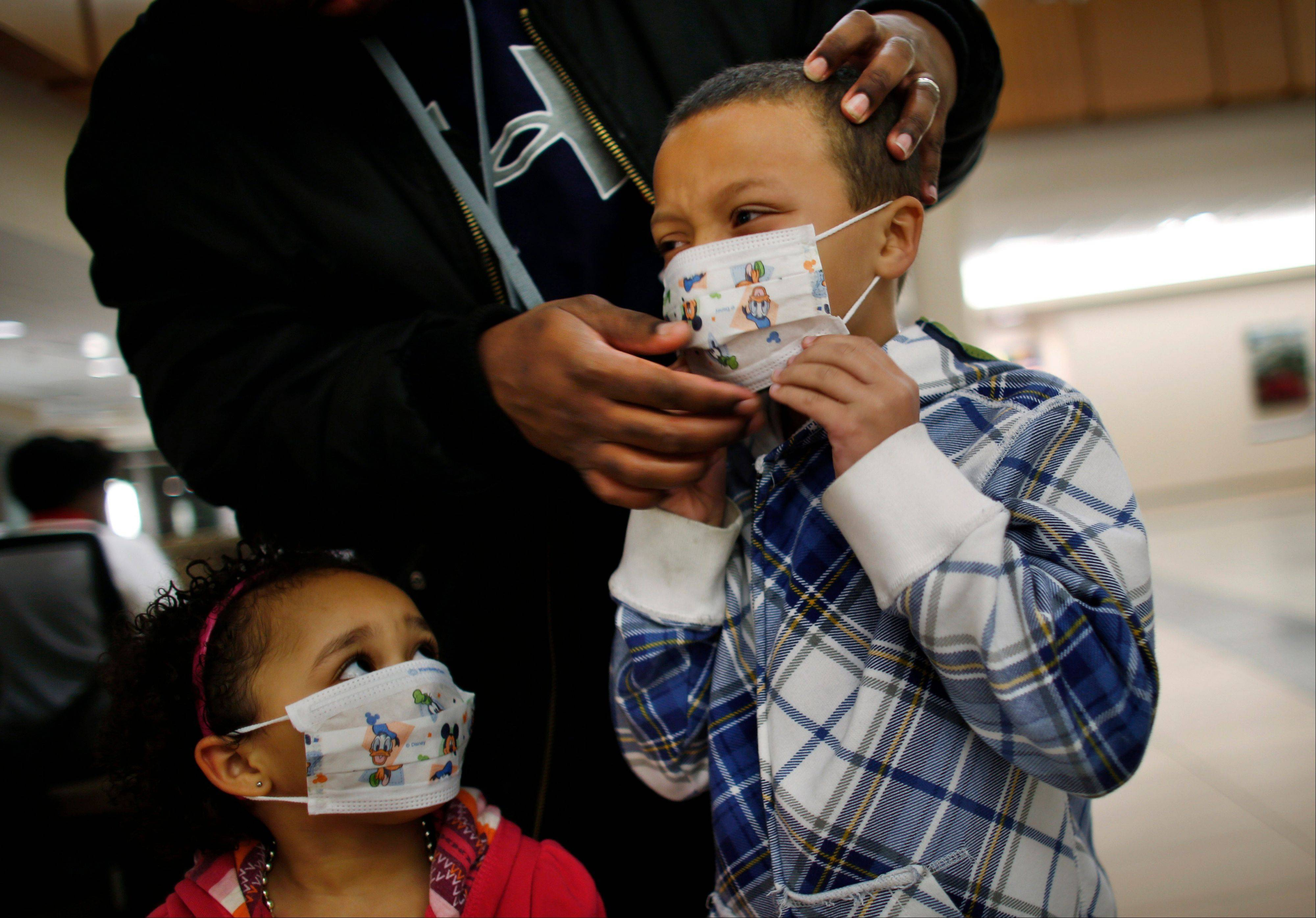 Associated Press/Jan. 9, 2013 Damien Dancy puts masks on his children Damaya, 3, left, and Damien, 7, at Sentara Princess Anne Hospital in Virginia Beach, Va., as hospitals in Hampton Roads are urging patients and visitors to wear a mask at their facilities to help stop the spread of the flu.