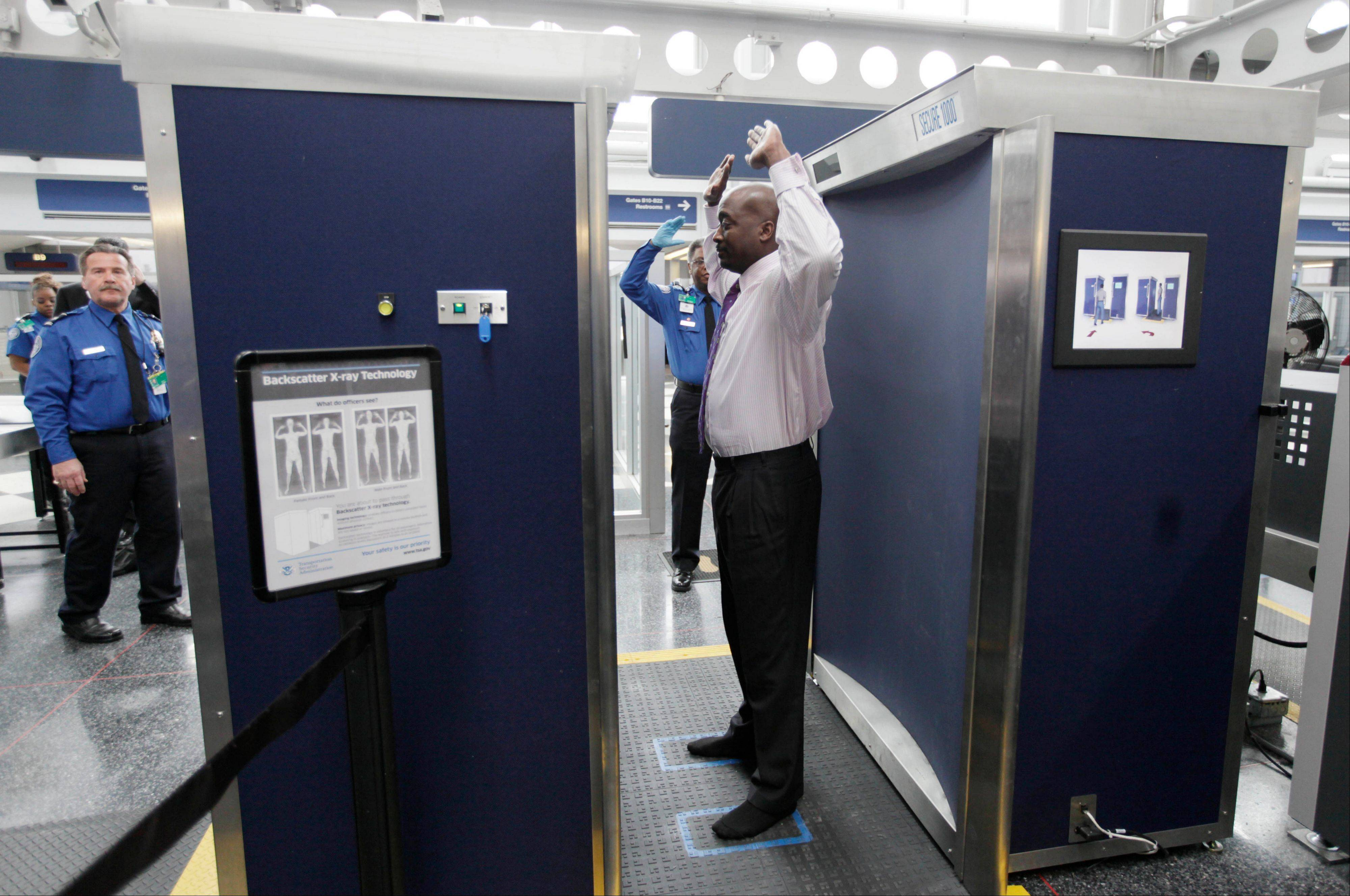 Volunteers pass through the first full body scanner, which uses backscatter technology, installed at O�Hare International Airport.
