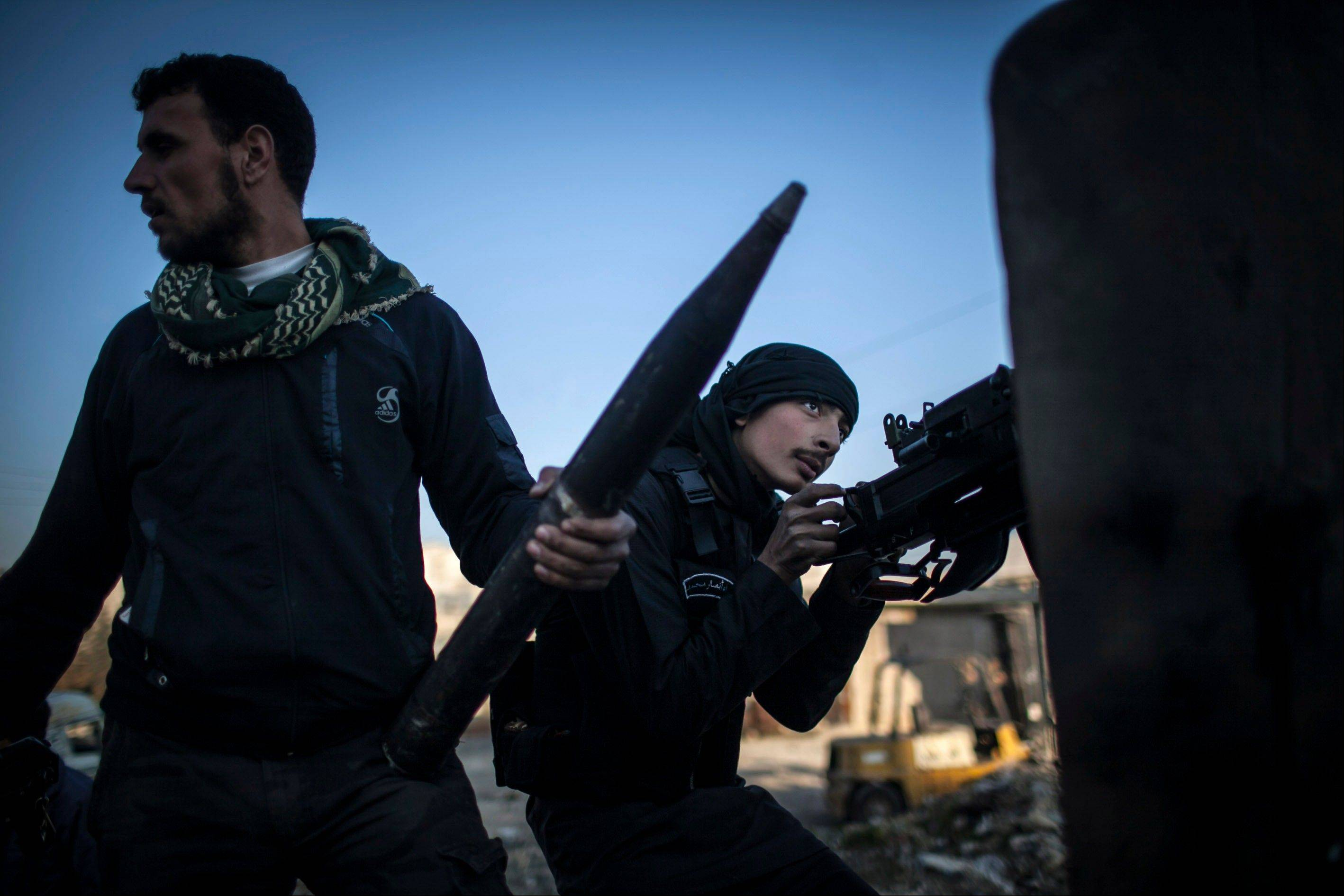 A Free Syrian Army fighter aims his weapon Tuesday during clashes with government forces in Aleppo, Syria.