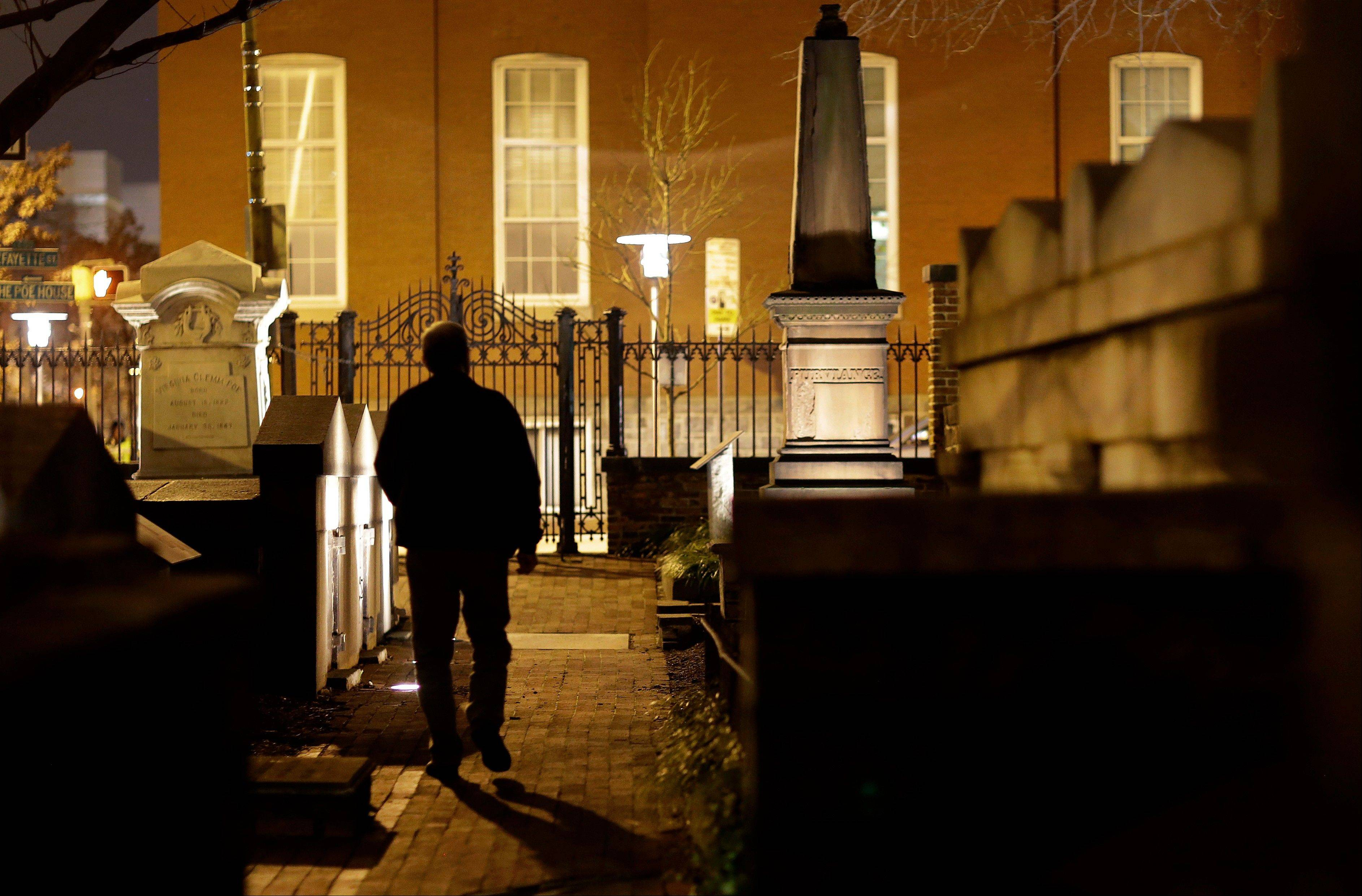 I Jeff Jerome walks Tuesday in a cemetery that is home to Edgar Allan Poe�s grave in Baltimore.