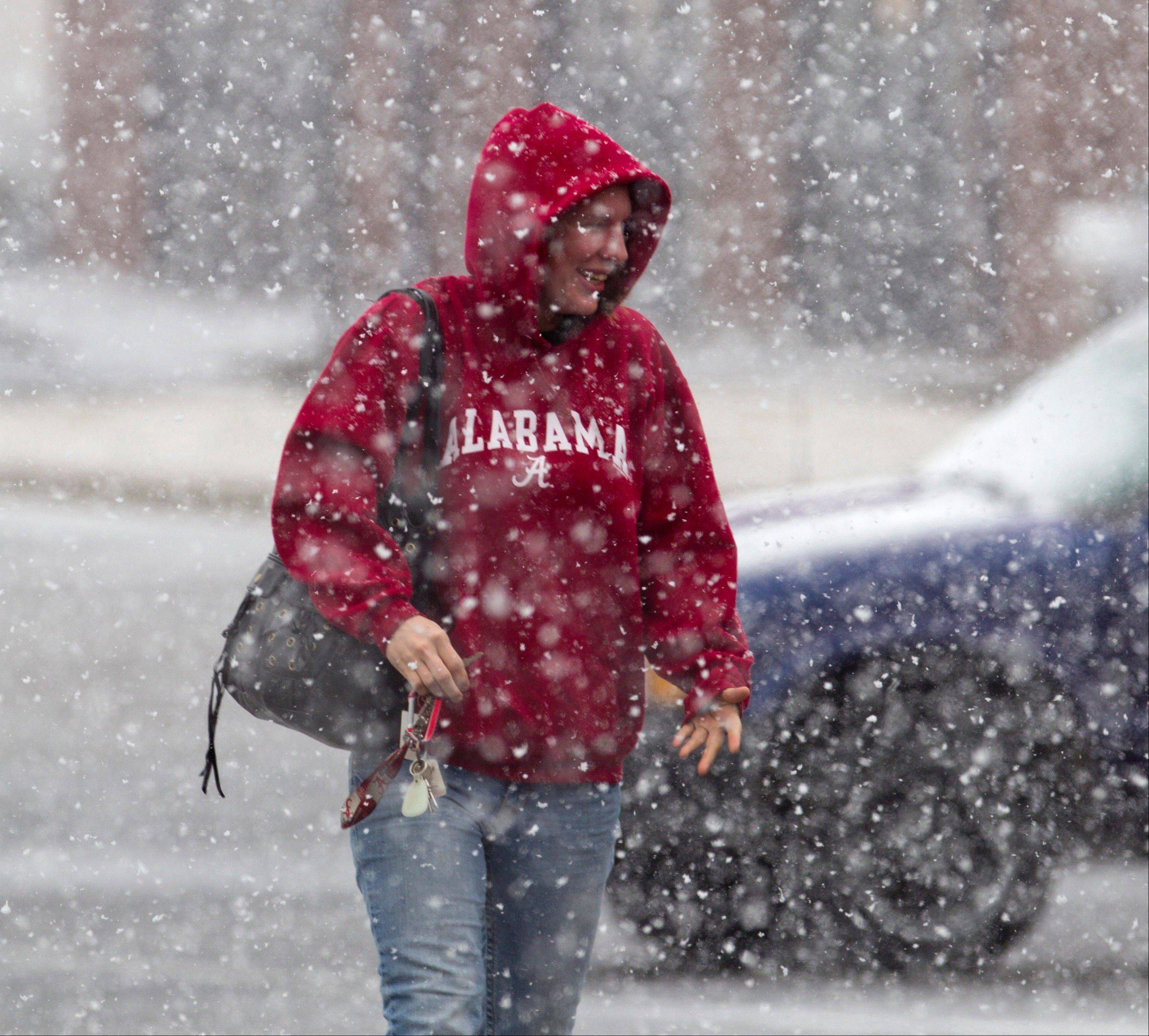 Brittany Fulmer walks through a snow storm Thursday in a mall parking lot in Florence, Ala.