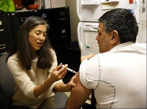 Dr. Julie Morita, Director of Immunizations at the Chicago Dept. of Public Health, gives Gary Chavarria a flu shot at a North Side clinic .