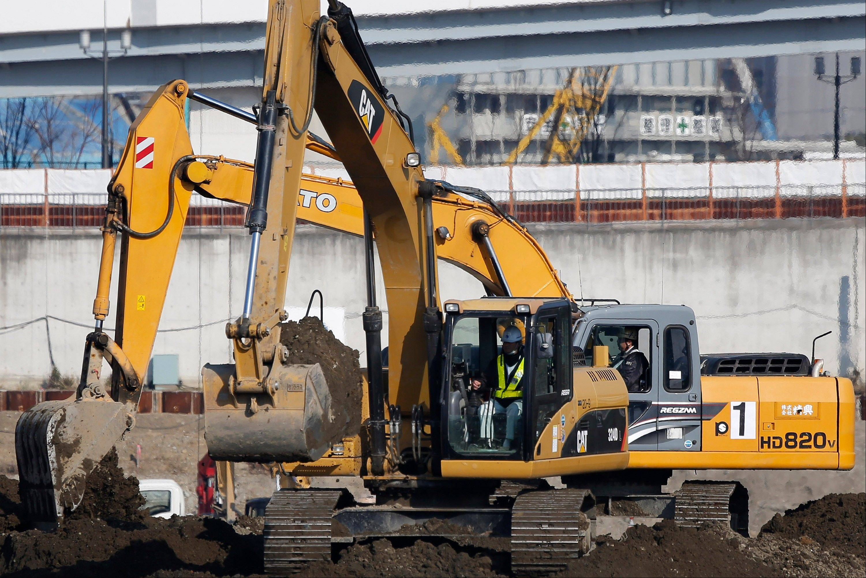A Caterpillar excavator, front, operates on a construction site in Tokyo, Japan.