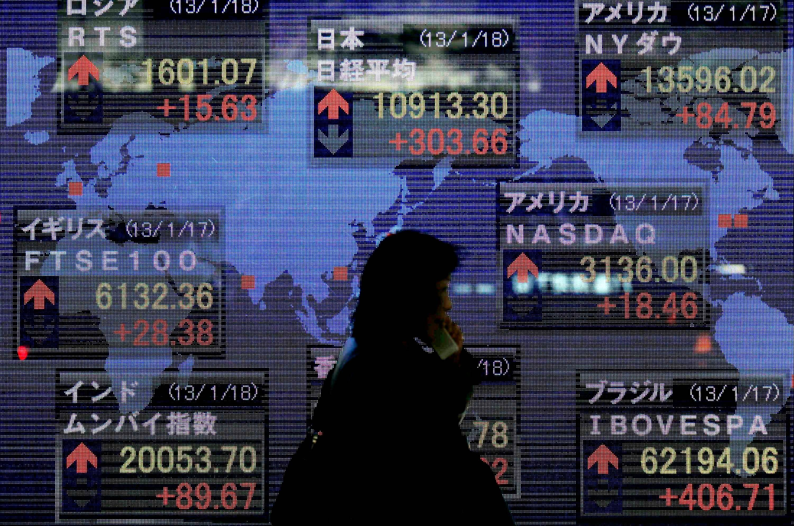 A woman walks by an electric stock index display of a securities firm in Tokyo, Friday.