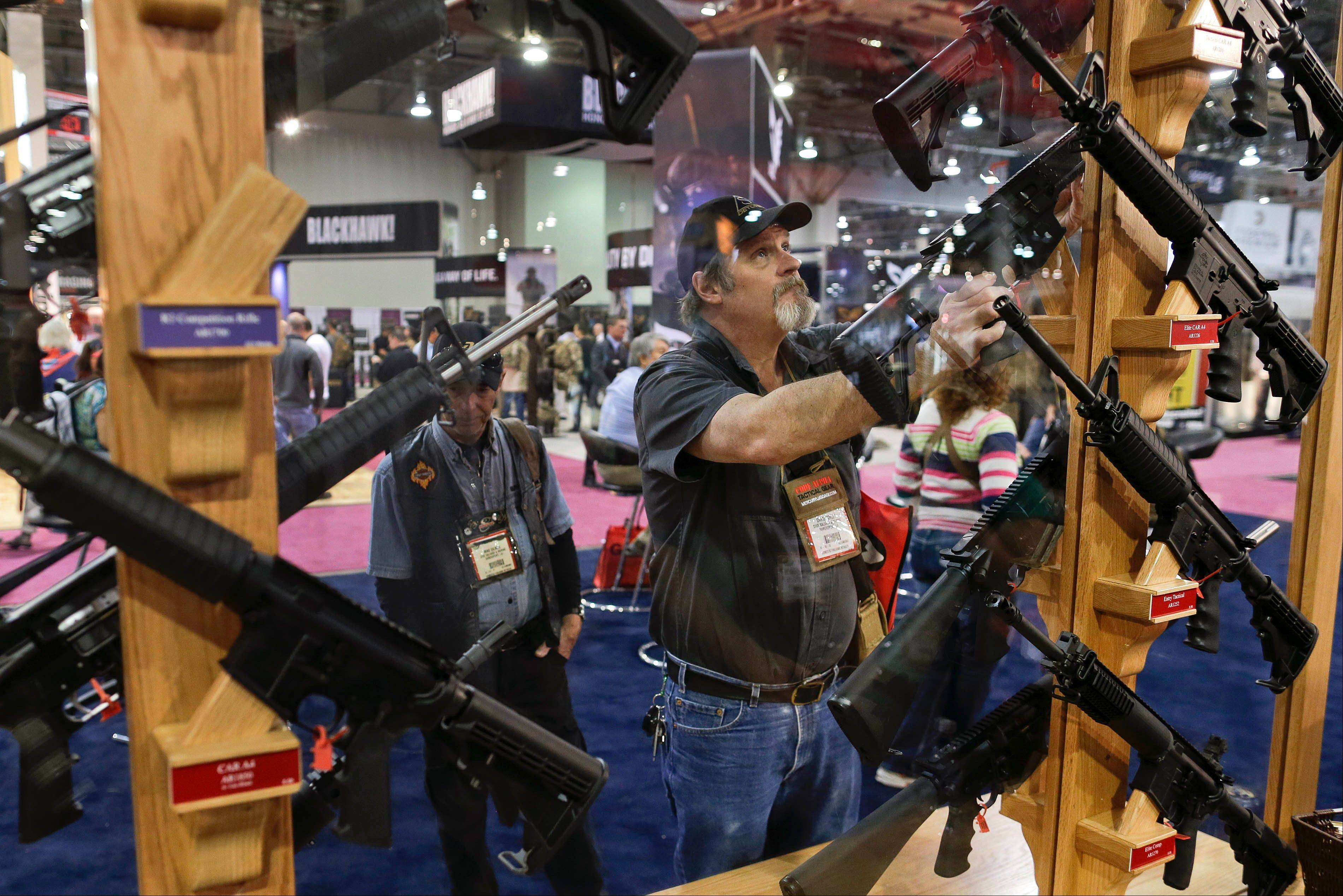 David Corley of Shreveport, La., replaces a rifle on its display rack Thursday while browsing through the Rock River Arms display booth at the 35th annual SHOT Show in Las Vegas. The world's largest gun and outdoor trade show ran through Friday.