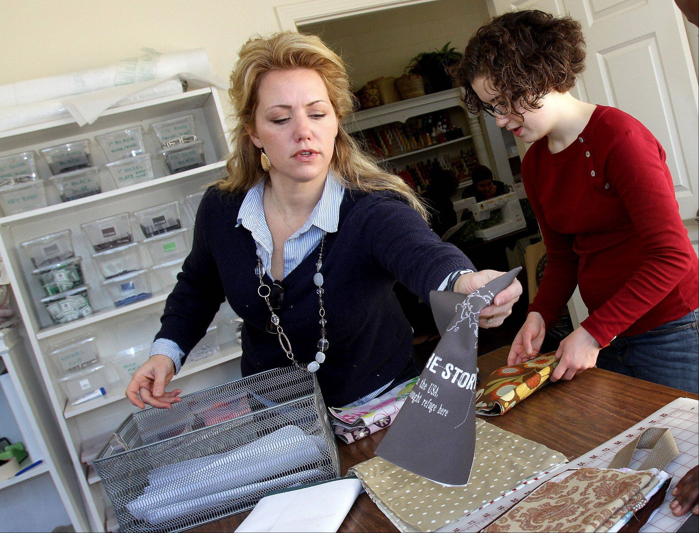 Sandberg, left, and volunteer Amy Bauer of Wheaton go over materials at the shop in Glen Ellyn.