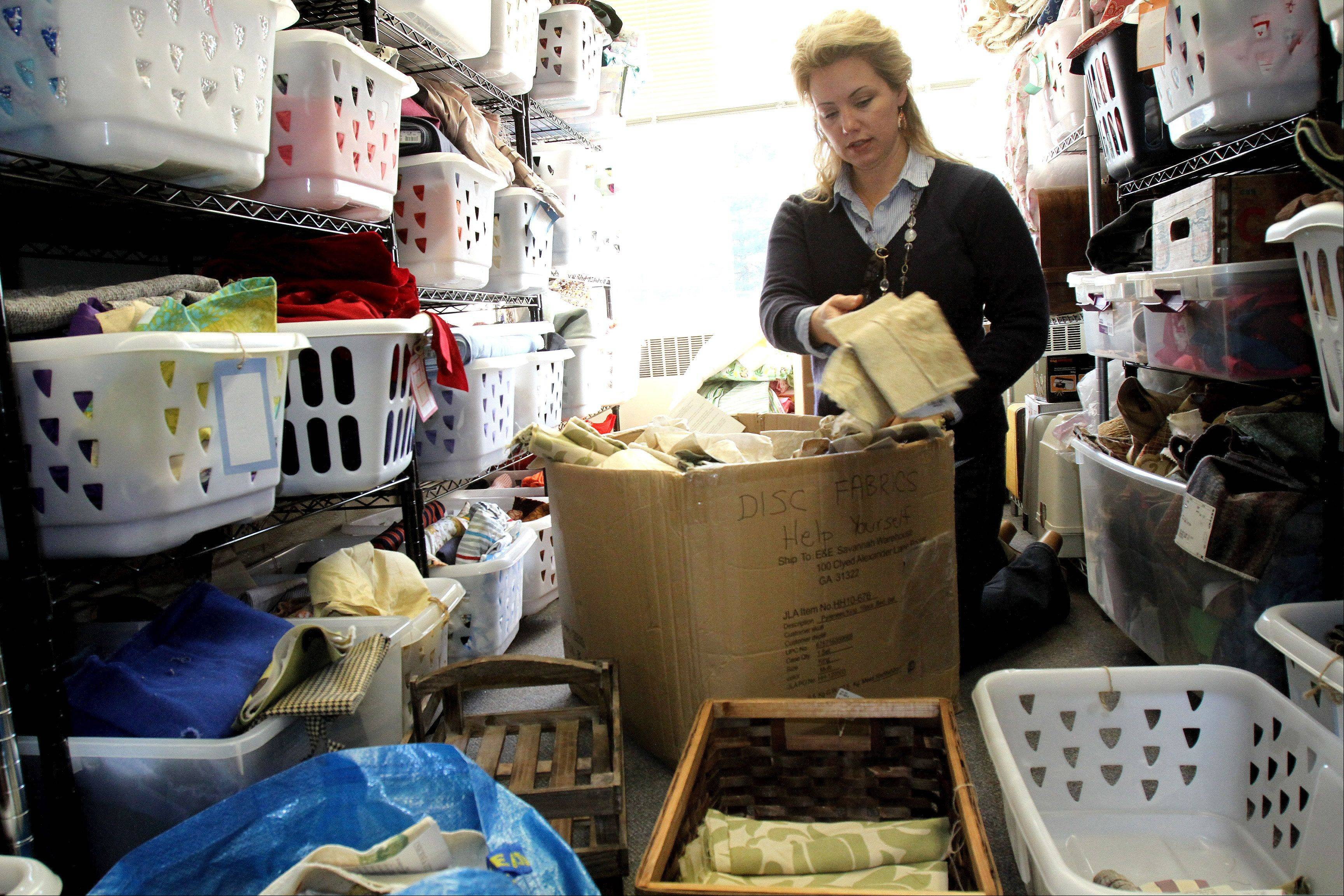 Rebecca Sandberg sorts through pieces of cloth, donated from Toms-Price furniture store, at her shop Re: new in Glen Ellyn. This store and others donate samples and materials to Re: new, which allows them to make their products.