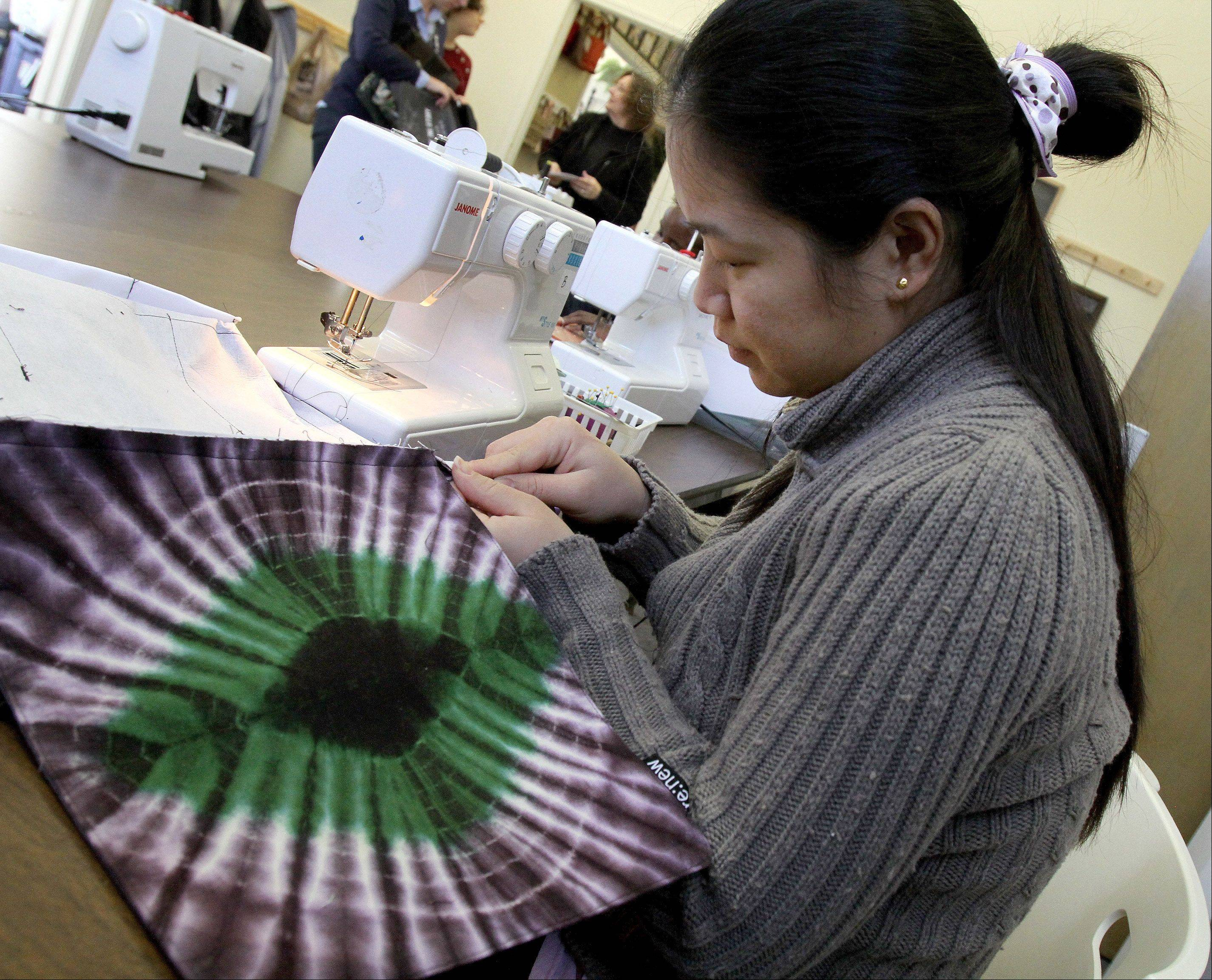 Esther Lahtaw of Wheaton, a refugee from Burma, works on a piece at Re: new in Glen Ellyn.