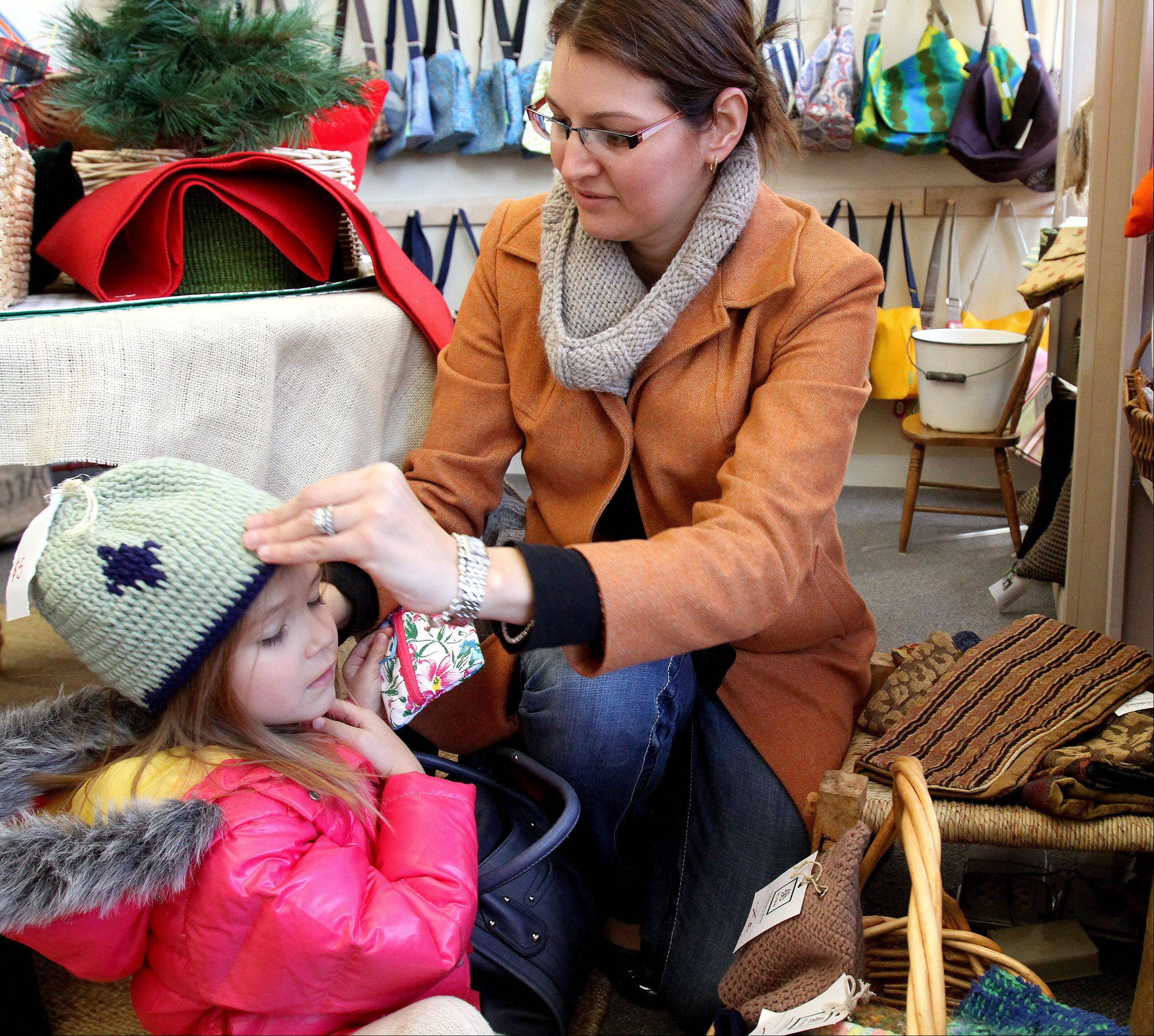Nicole Smulkstys of Glen Ellyn tries a hat on her daughter Kara, 3, as they shop at Re: new in Glen Ellyn. All the items in the shop are made by refugee women employed by Re: new who work right next to the store.