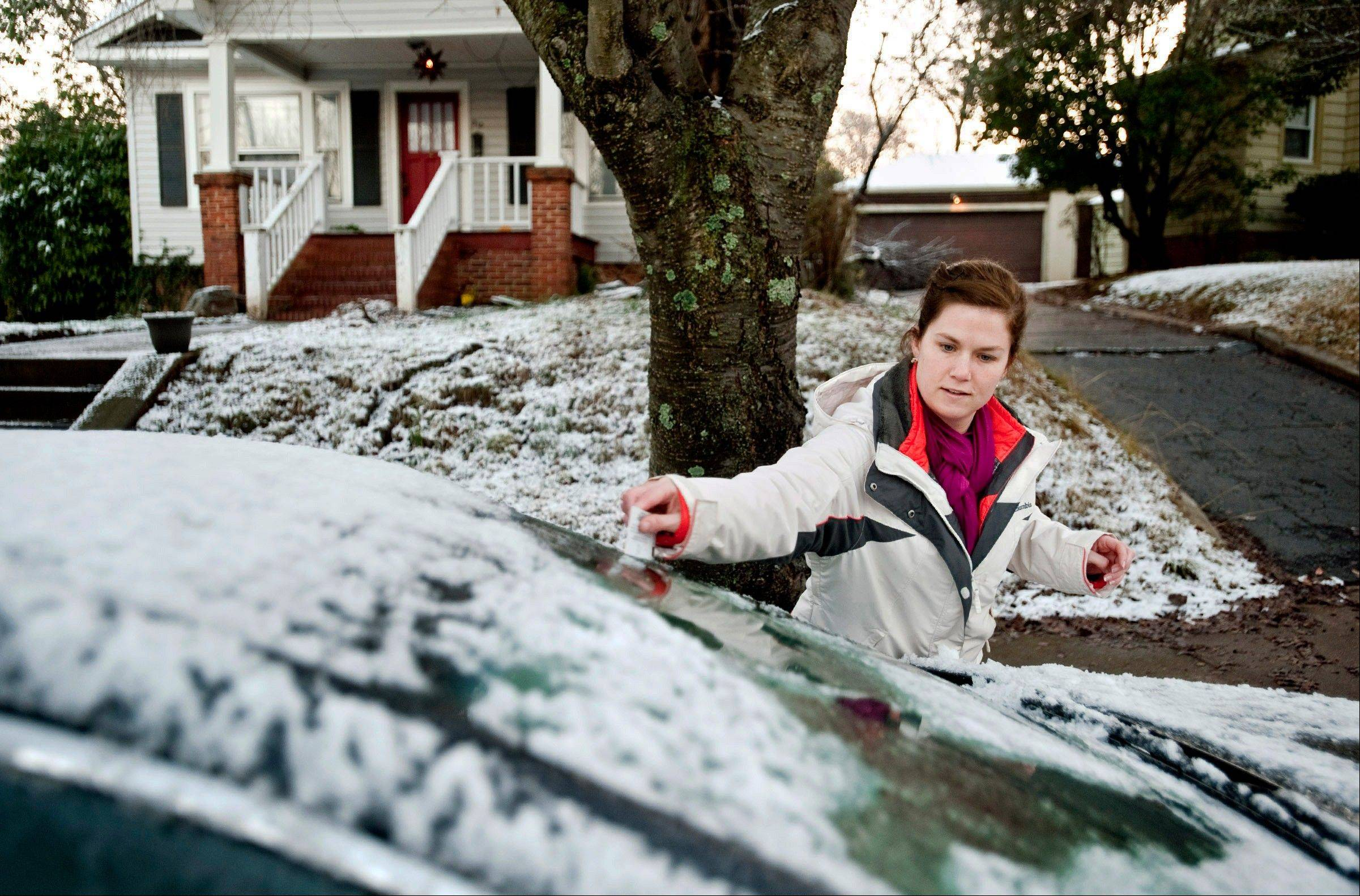 Erin Hull, of Winston-Salem, uses gift cards from her wallet to scrape ice and snow off her car before going to work Friday, Jan. 18, 2013, in Winston-Salem, N.C. Hull says she would have used her ice scraper, but it was inside her frozen-shut trunk.