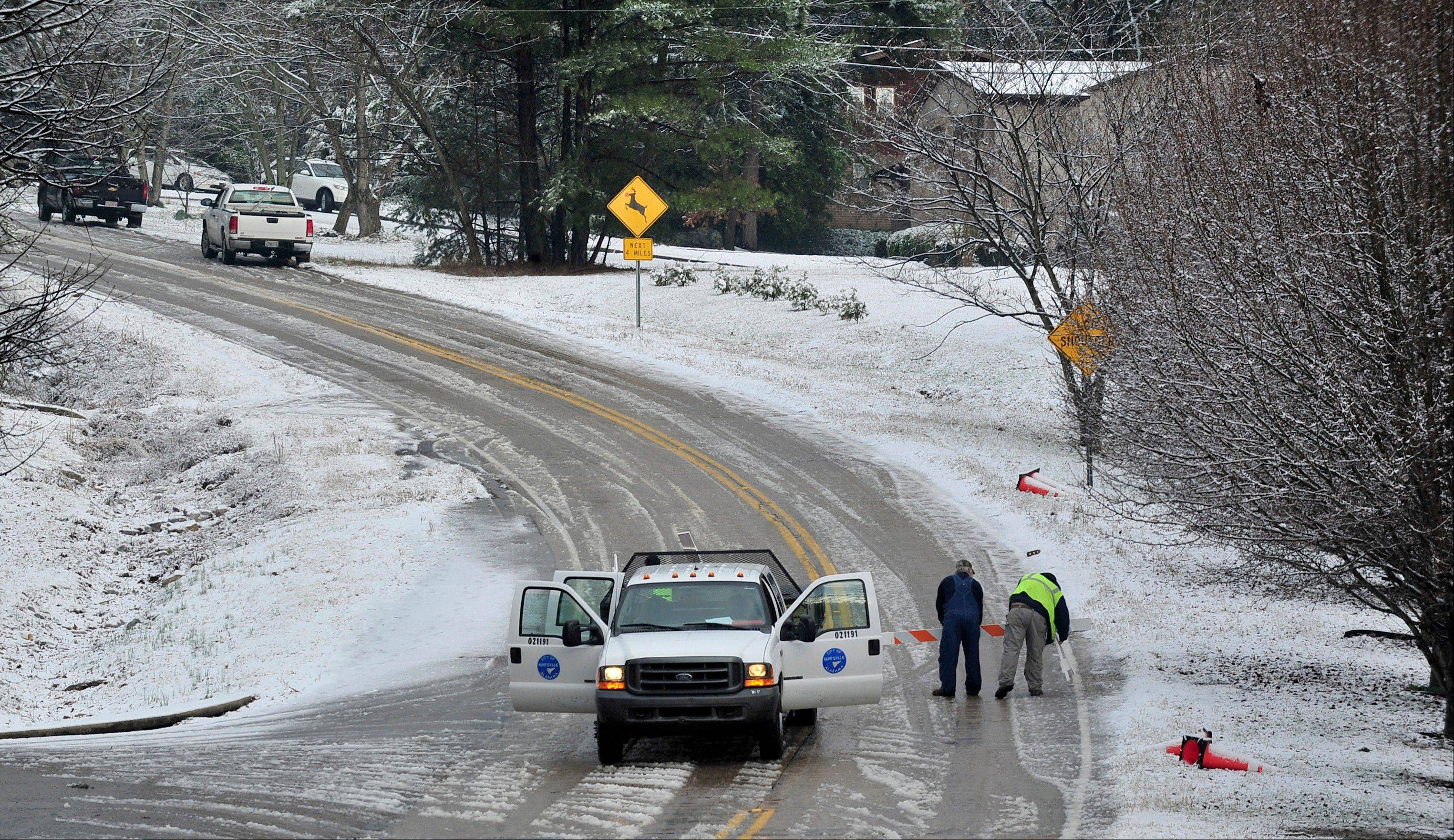City of Huntsville workers set up road blocks on Green Mountain Road while a salt truck clears the road during a brief winter storm which brought light snow and icy roads to north Alabama Thursday, Jan. 17, 2013 in Huntsville, Ala. A winter storm made its way across the Southeast on Thursday, dumping snow in states recovering from days of rain, playing a role in at least one fatality, and leaving thousands without power.