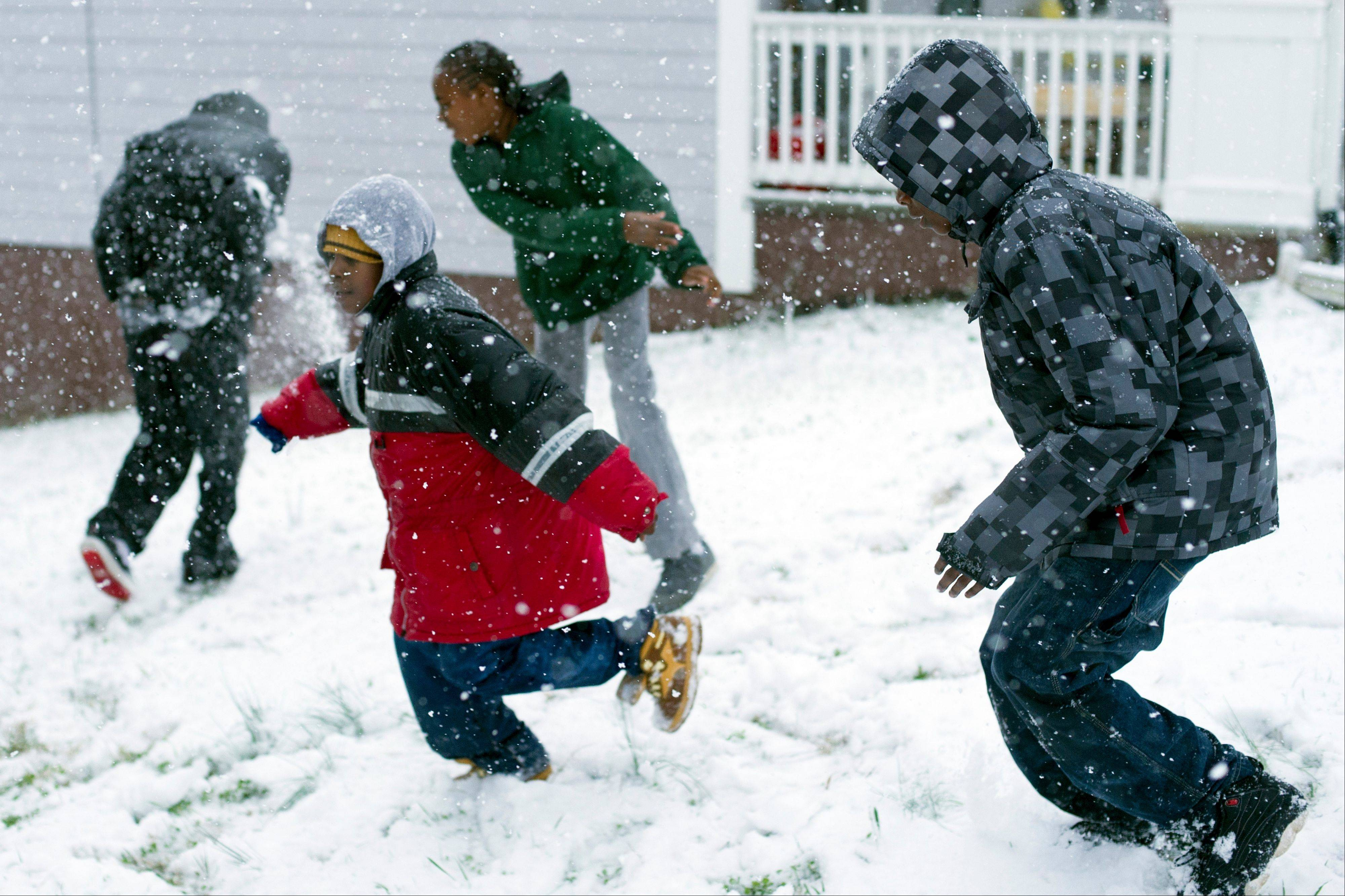 Children play in the snow Thursday, Jan. 17, 2013, in Knoxville, Tenn. A winter storm was making its way across the Southeast on Thursday, dumping 4 inches of snow in Mississippi and playing a role in a traffic fatality there, with the system expected to spread across northern Georgia and into the Carolinas and Virginia, according to the National Weather Service.