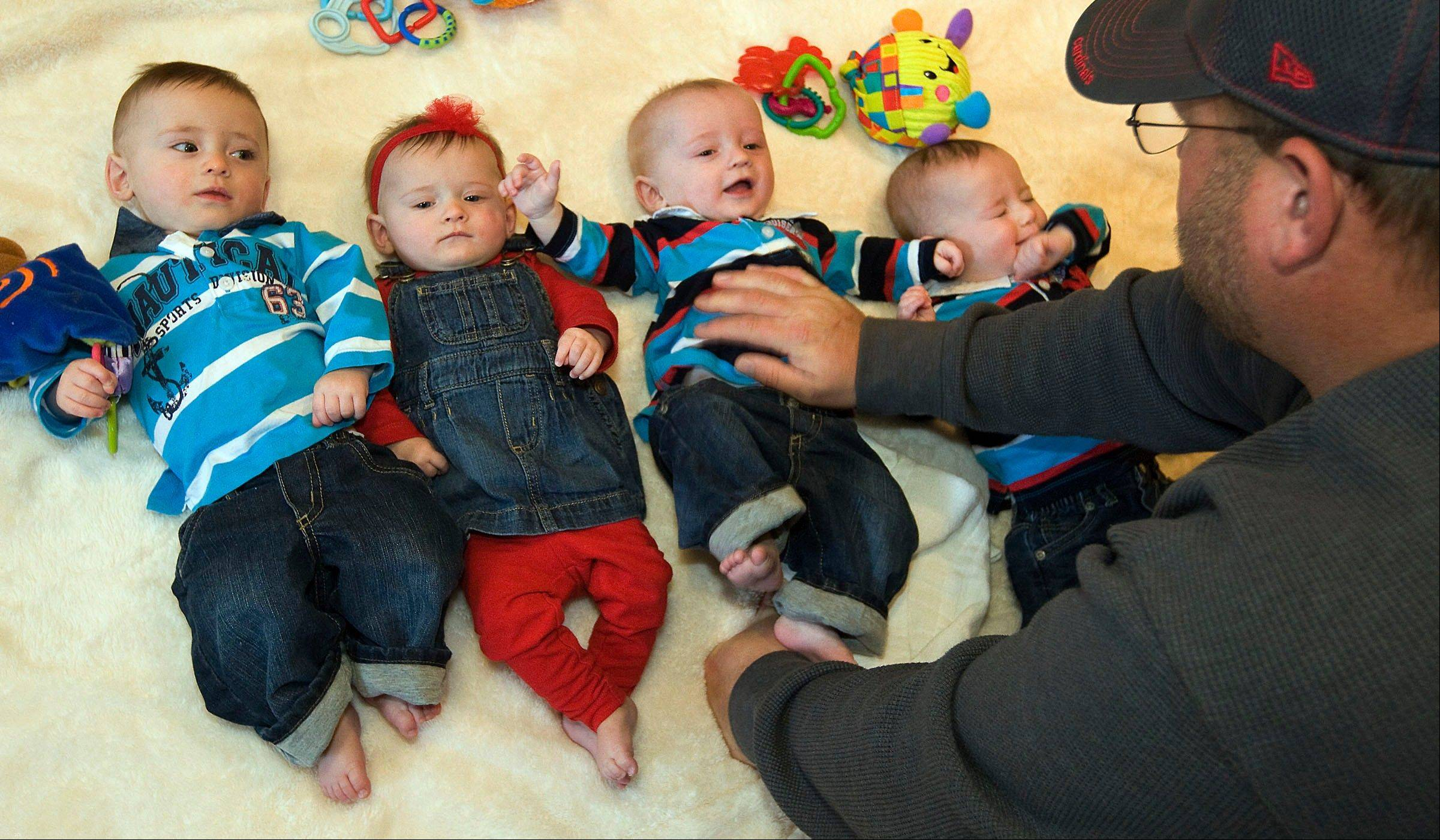 Jesse Burnett plays with his quadruplets from left, Jaleb, Jianna, Jace and Jacoby at their home of Lovington.
