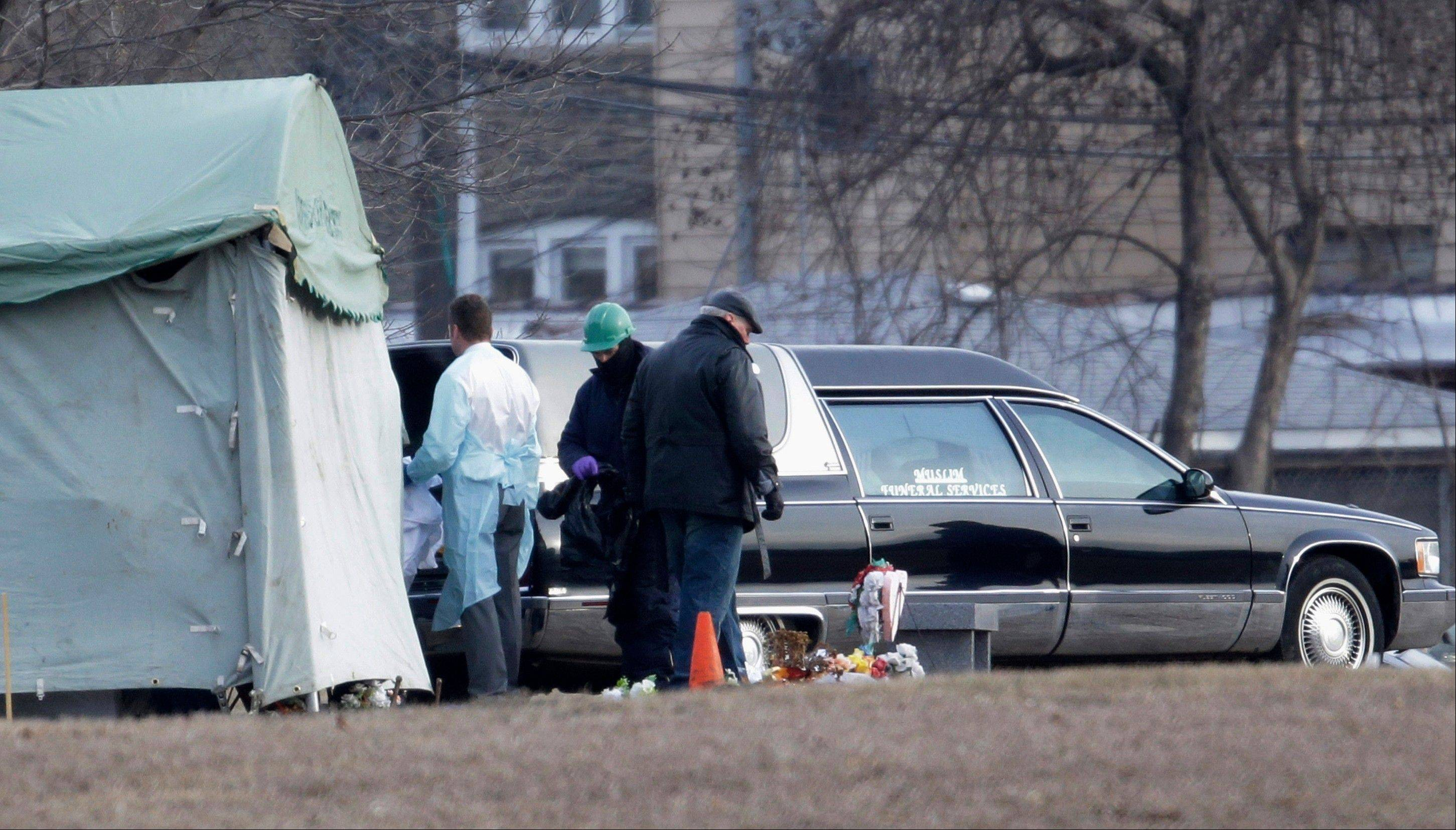 Workers at Rosehill Cemetery in Chicago place the body of Urooj Khan into a hearse after it was exhumed Friday for an autopsy to help solve the mystery surrounding his death.