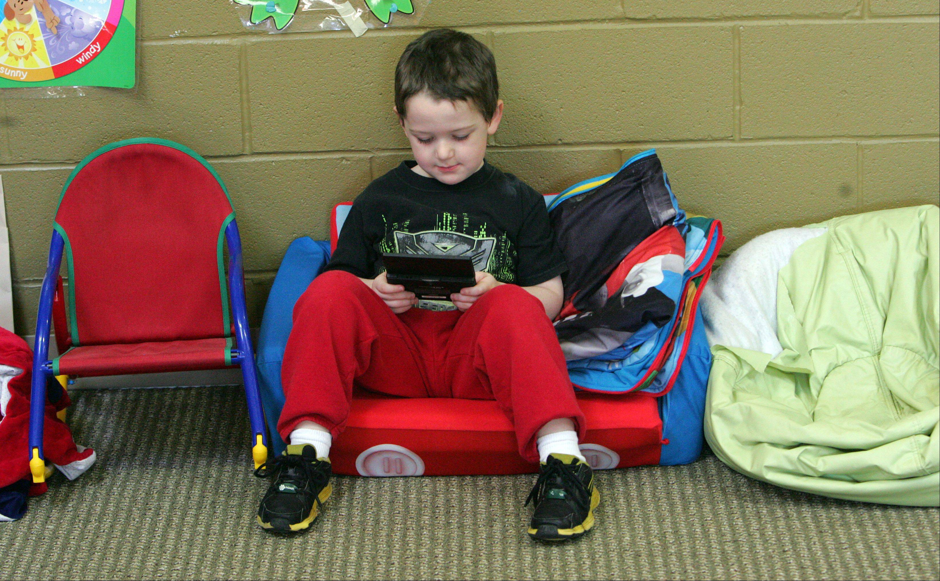 4-year-old Oliver Blennis of Grayslake plays a computer game during Strike Camp at the Grayslake Park District Recreation Center Thursday morning. The Strike Camp will be open today, too.