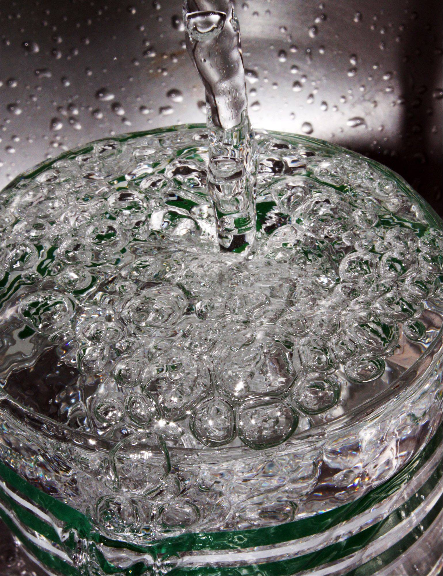 Bubbles erupt from a glass in a kitchen sink as water pours in.