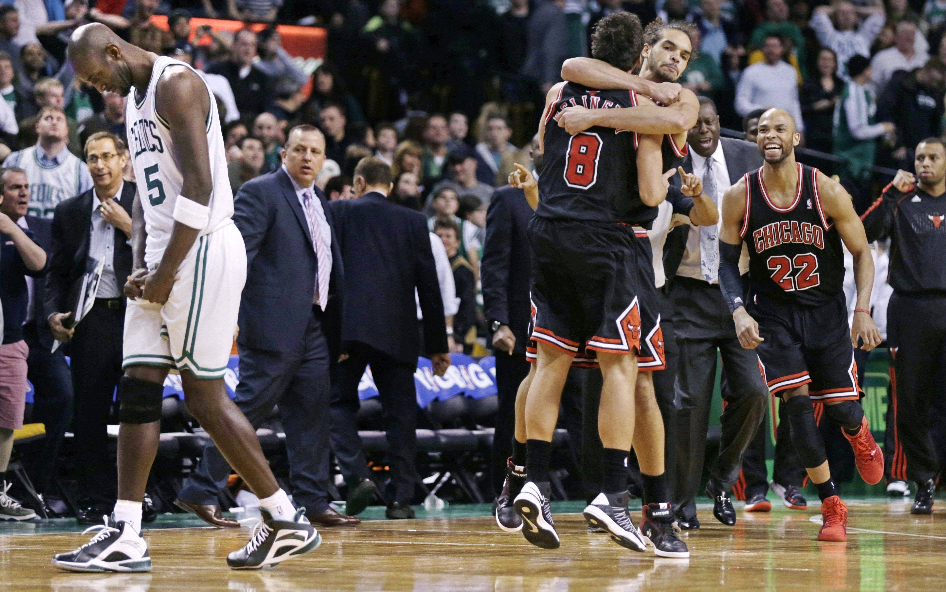 As Boston Celtics forward Kevin Garnett, left, walks off the court, Chicago Bulls guard Marco Belinelli (8) is congratulated by teammate Joakim Noah after an overtime win Friday in Boston. Belinelli hit the go-ahead basket less than 4 seconds on the clock.