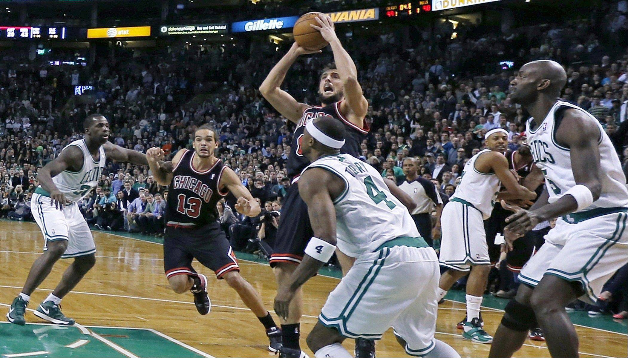 Bulls guard Marco Belinelli, center, puts up the game-winning basket in the final seconds of overtime against the Celtics Friday in Boston.
