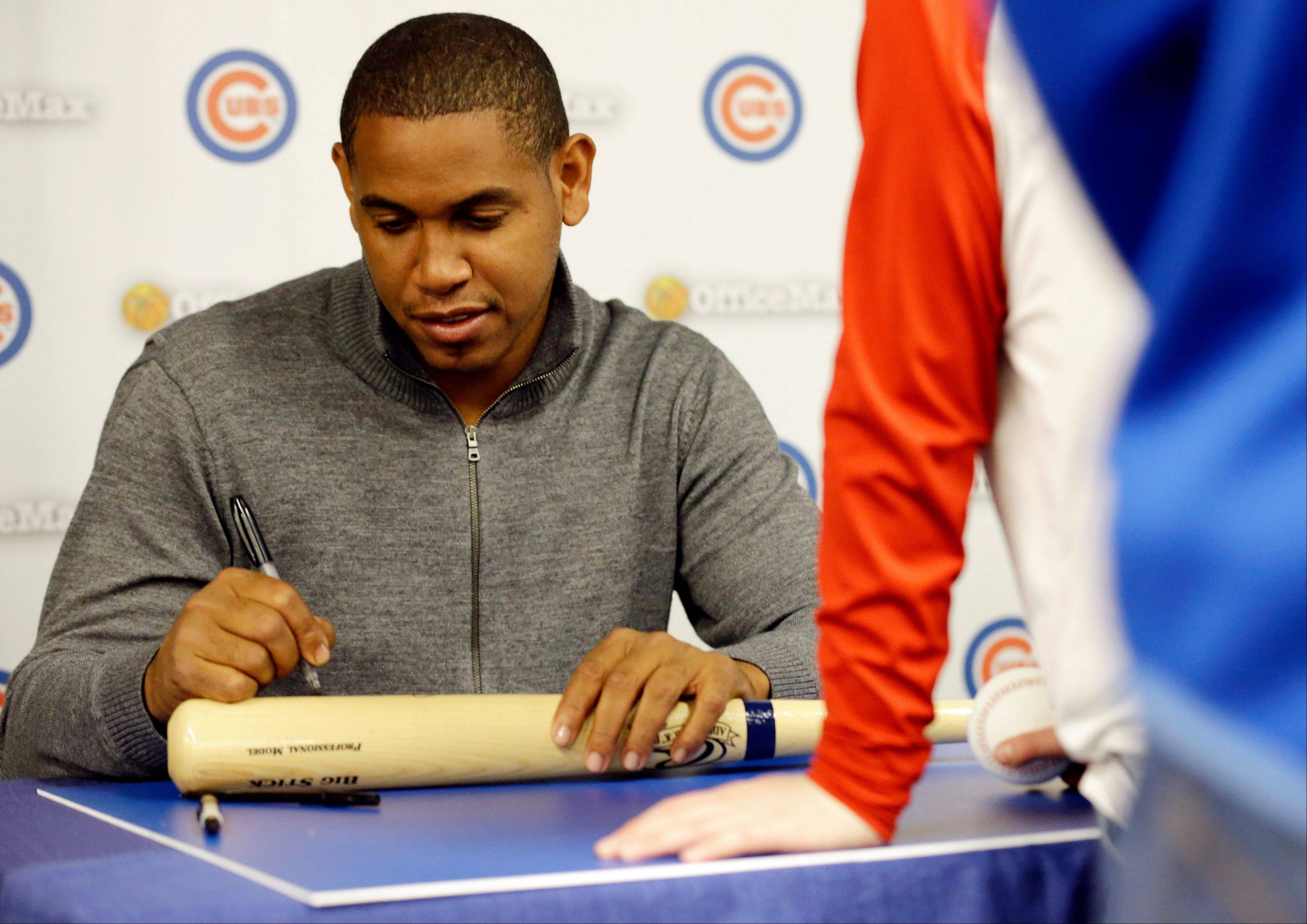 Cubs pitcher Carlos Marmol signs autographs for fans during the Cubs Convention on Friday in Chicago.