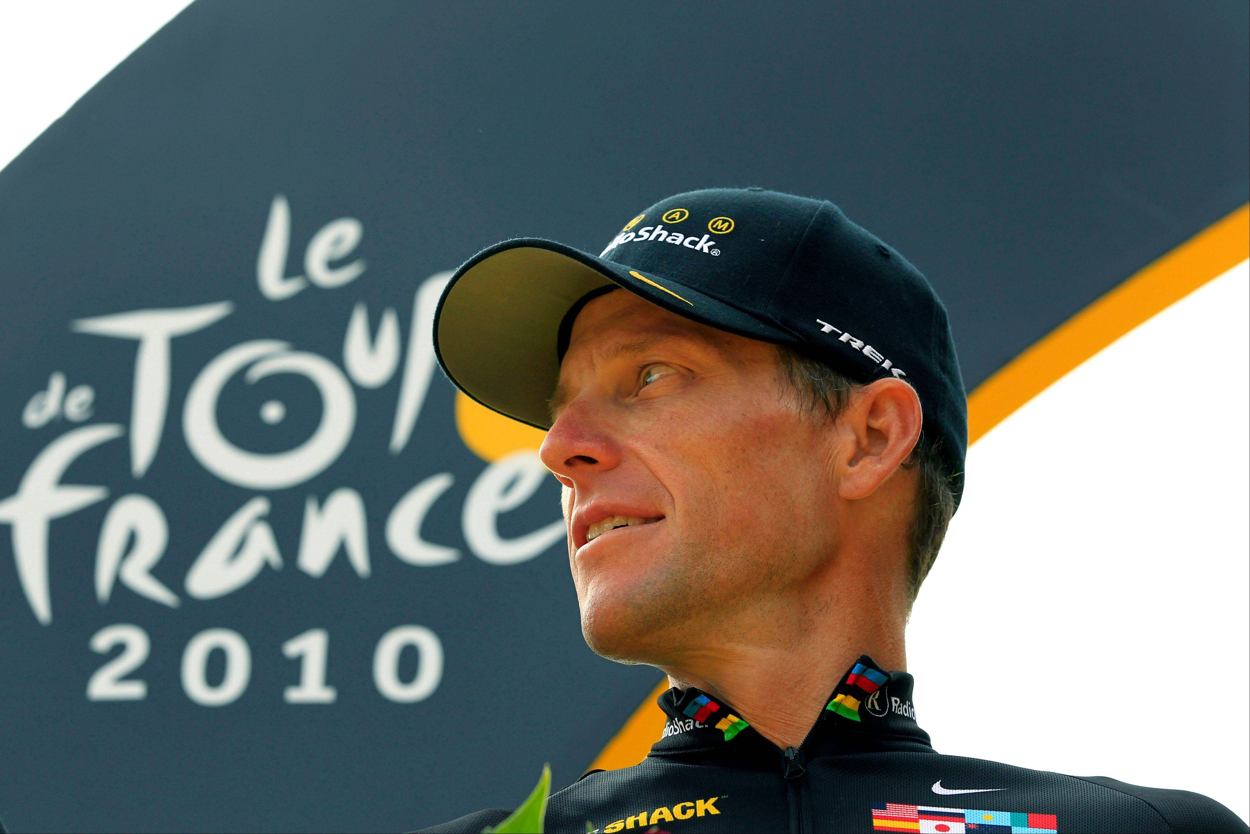 Lance Armstrong looks back on the podium after the final stage of the Tour de France in 2010. Armstrong confessed to using performance-enhancing drugs to win the Tour de France during a taped interview with Oprah Winfrey that aired Thursday.