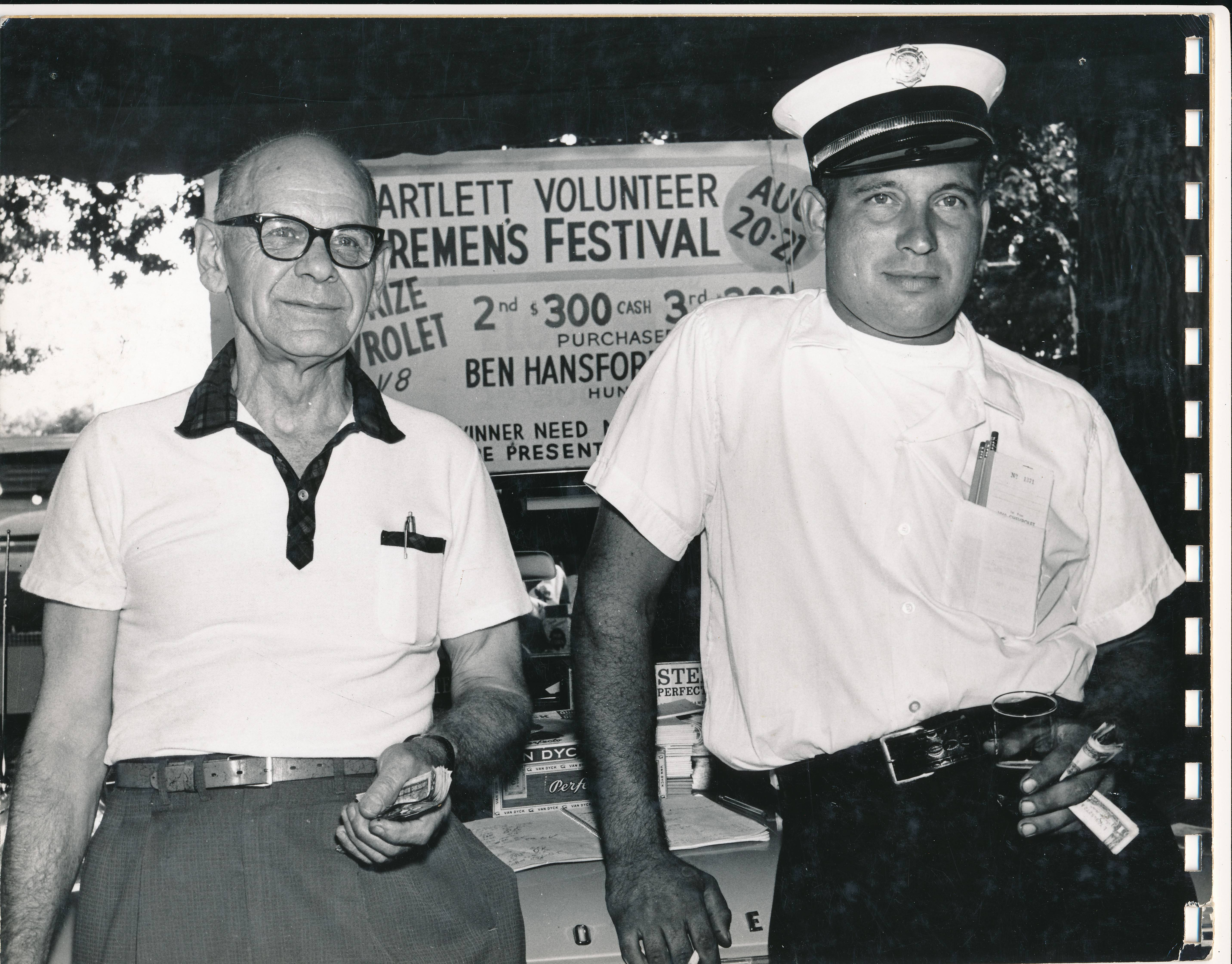 With cash in hands, Bill Schultz, left, and Bob Van Alstine, right, are selling raffle tickets at the 1960 Bartlett Firemen's Festival. First prize was a car!