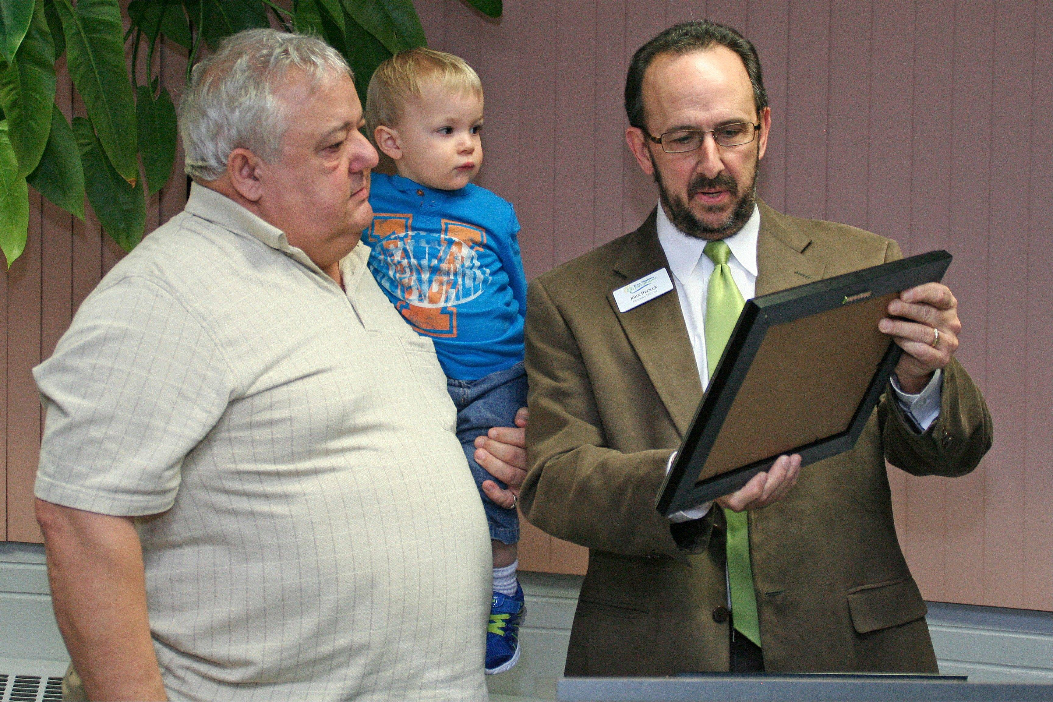 Commissioner Donald J. Rosedale, holding his grandson, John Skibbe, receives the Community Service Honor Roll Award from Des Plaines Park District Executive Director John Hecker.