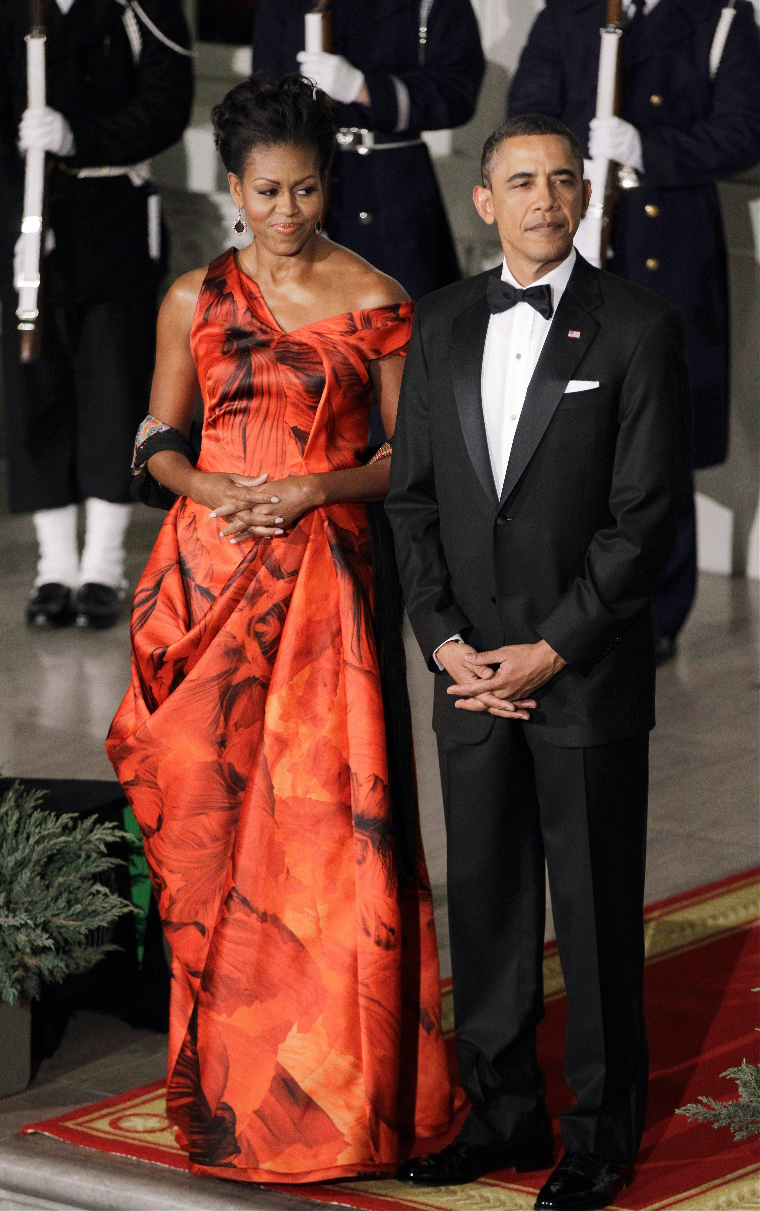 President Barack Obama and first lady Michelle Obama at the North Portico of the White House in Washington during a State Dinner for China's President Hu Jintao. Michelle Obama is wearing a fiery red gown designed by Alexander McQueen.