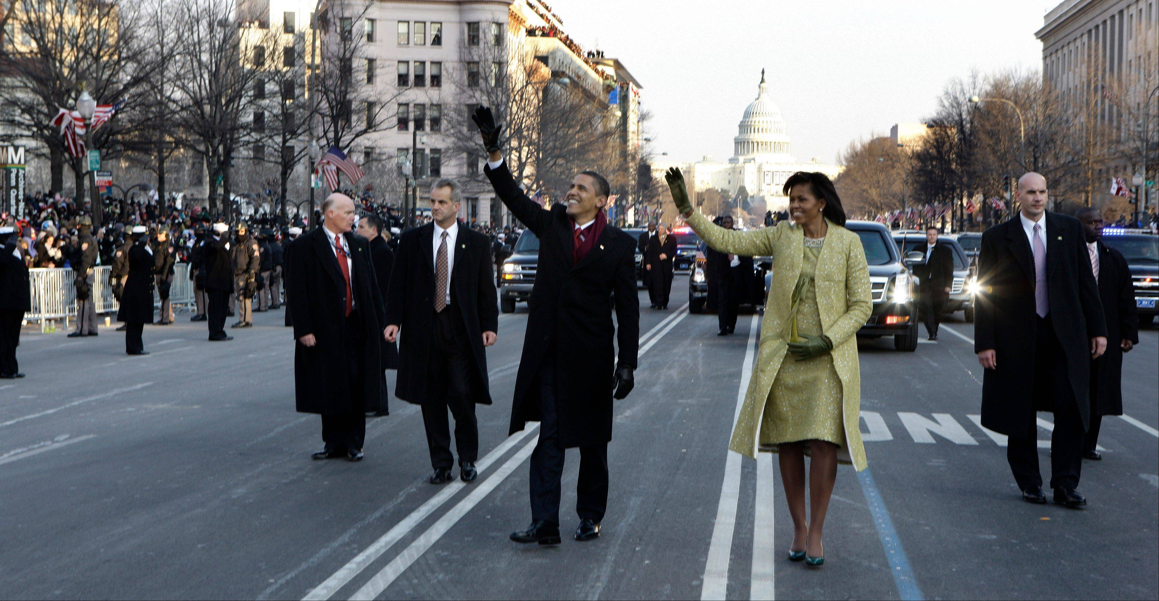 President Barack Obama and first lady Michelle Obama wave as they walk down Pennsylvania Avenue en route to the White House from the Capitol in Washington on Jan. 20, 2009.