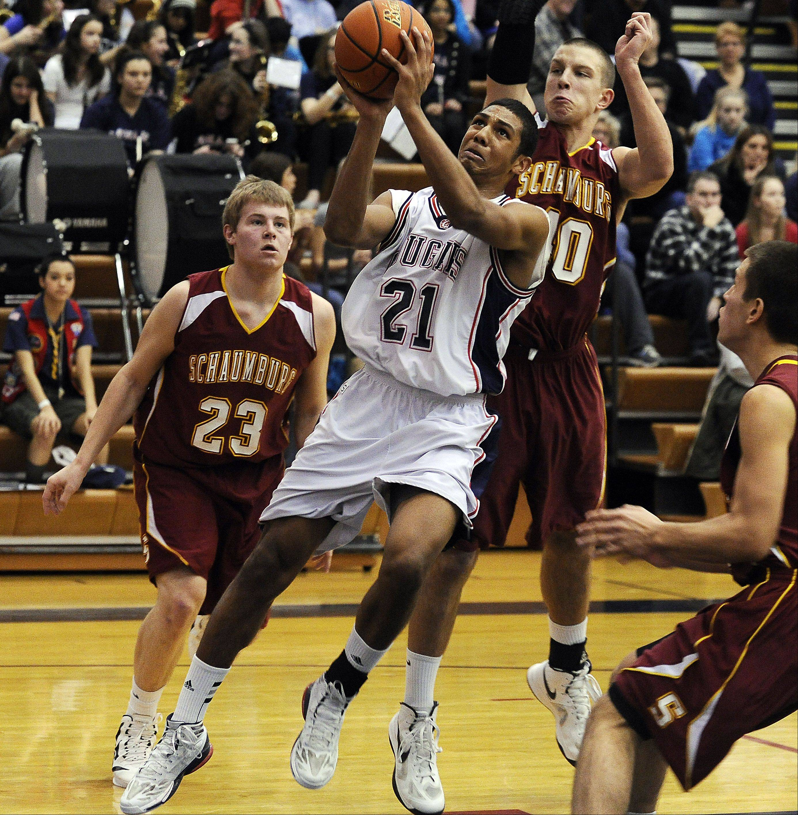 Conant�s D�Angelo McBride drives around Schaumburg defenders for a bucket in the first half at Conant on Saturday.
