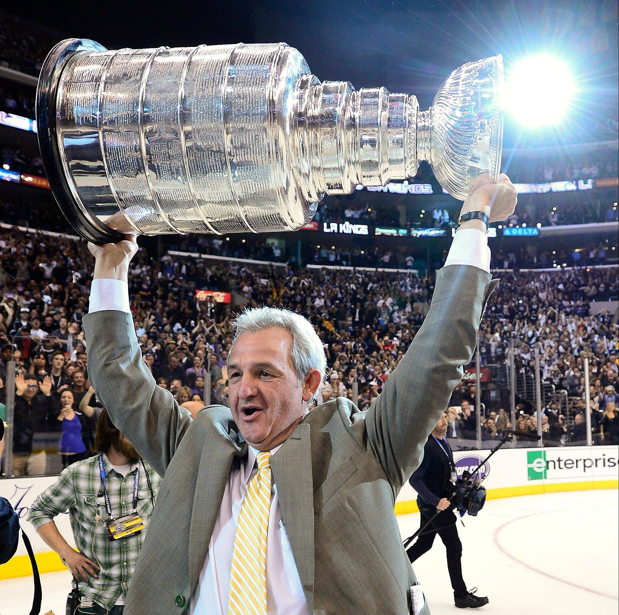 Coach Darryl Sutter hoists the Stanley Cup after the Los Angeles Kings beat the New Jersey Devils 6-1 in Game 6 of the Stanley Cup Finals last season. Sutter, who coached the Hawks for three seasons from 1992-95, and the Kings host the Hawks today.