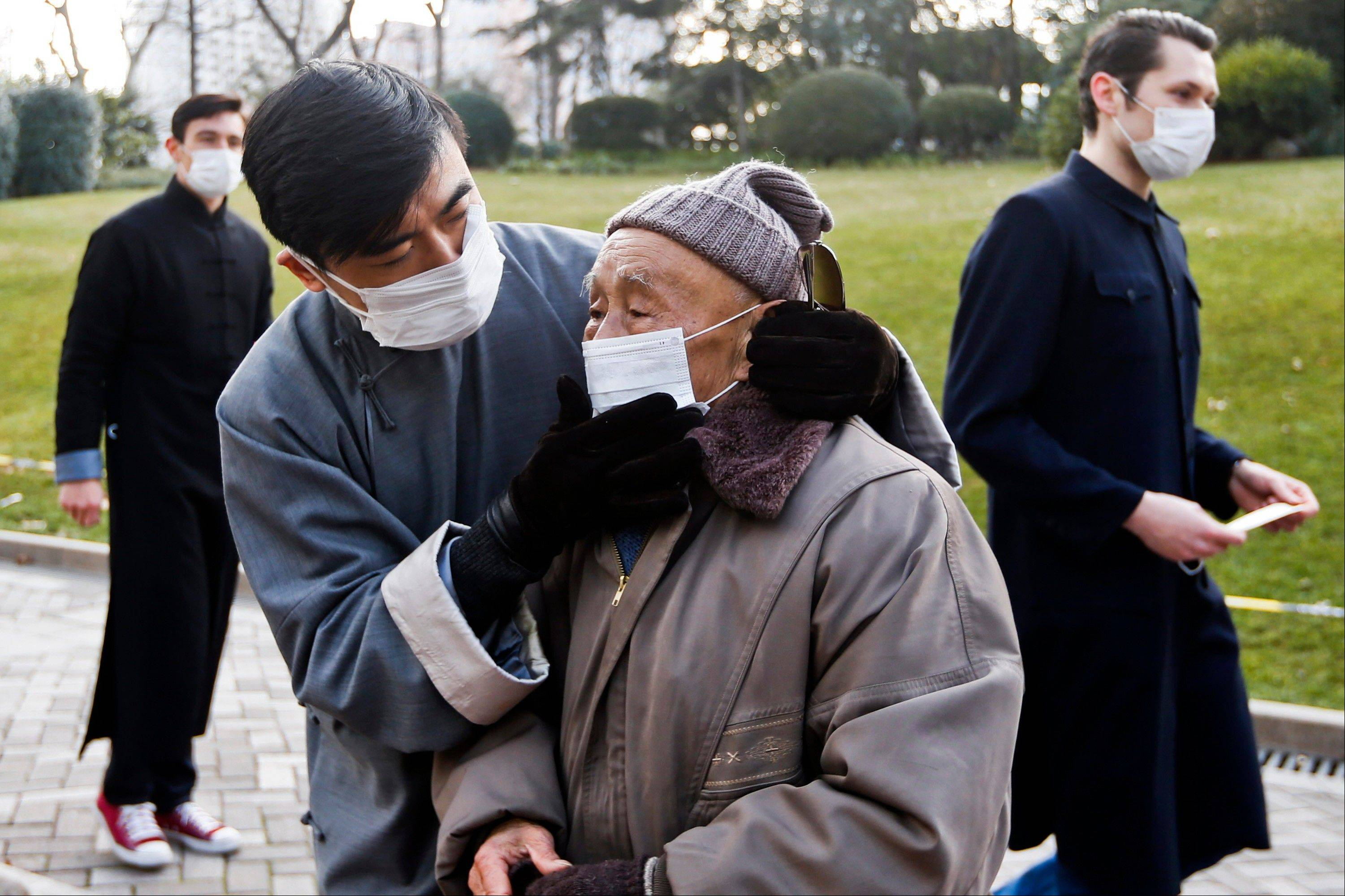 A man helps put on a mask for an elderly passer-by while several foreigners hand out free masks to pedestrians without masks in an effort to promote public awareness to use masks for protection from polluted air in downtown Shanghai. Air pollution is a major problem in China.