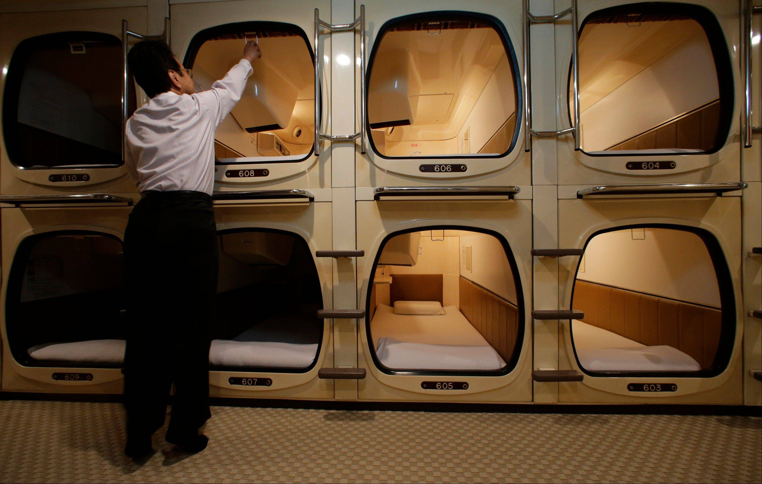 Photo, manager Akiyoshi Kaneko checks out one of the capsule rooms at the Capsule & Sauna Century Shibuya in Tokyo.