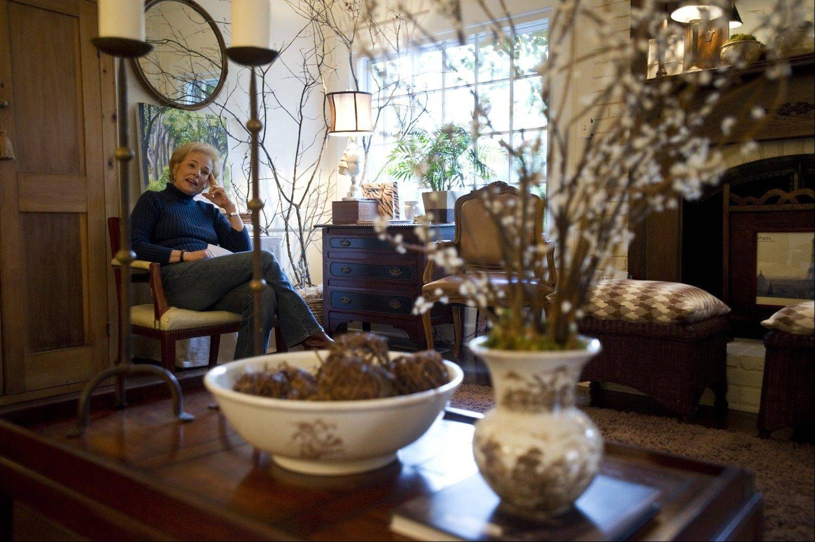 Kaye McWhorter is seen behind a coffee table she purchased for $10 at an estate sale. The McWhorter home is filled with thoughtfully re-purposed found items and thrift store bargains.