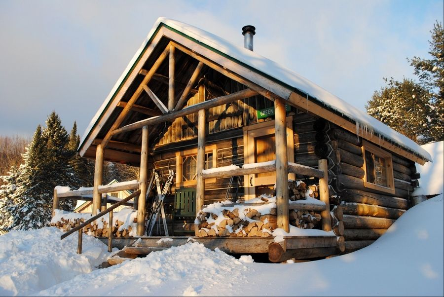 A rustic cabin in the snow at the Appalachian Mountain Club's Little Lyford Lodge and Cabins, a backcountry wilderness lodge. In winter, visitors can reach the lodges and cabins only by cross-country skiing in.