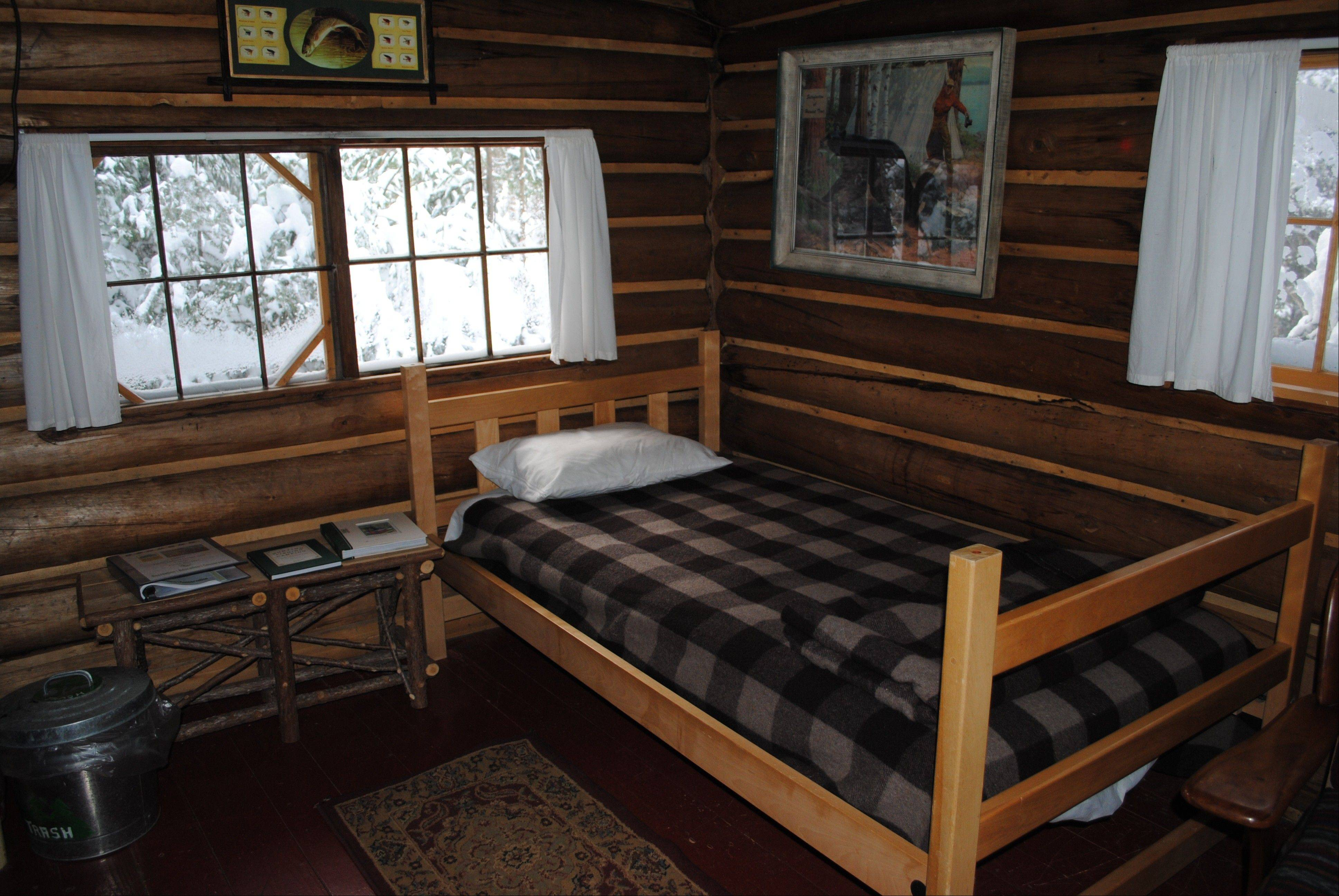 The interior of a rustic cabin at Little Lyford Lodge and Cabins. The cabin has no electricity, is heated by a wood stove and lit by gas lamp.