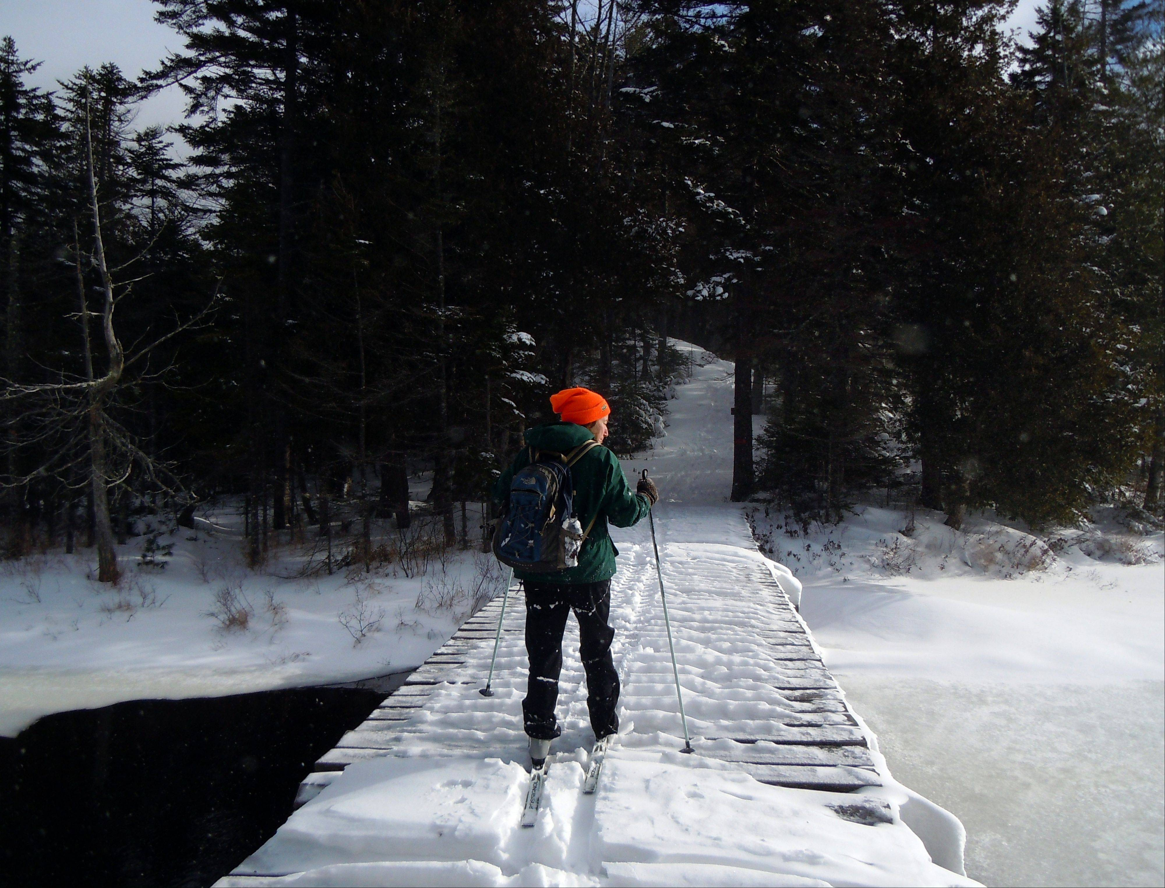 Lynn Dombek cross-country skis over a bridge on the lodge to lodge trail between camps at the Appalachian Mountain Club's backcountry wilderness lodge near Greenville, Maine.