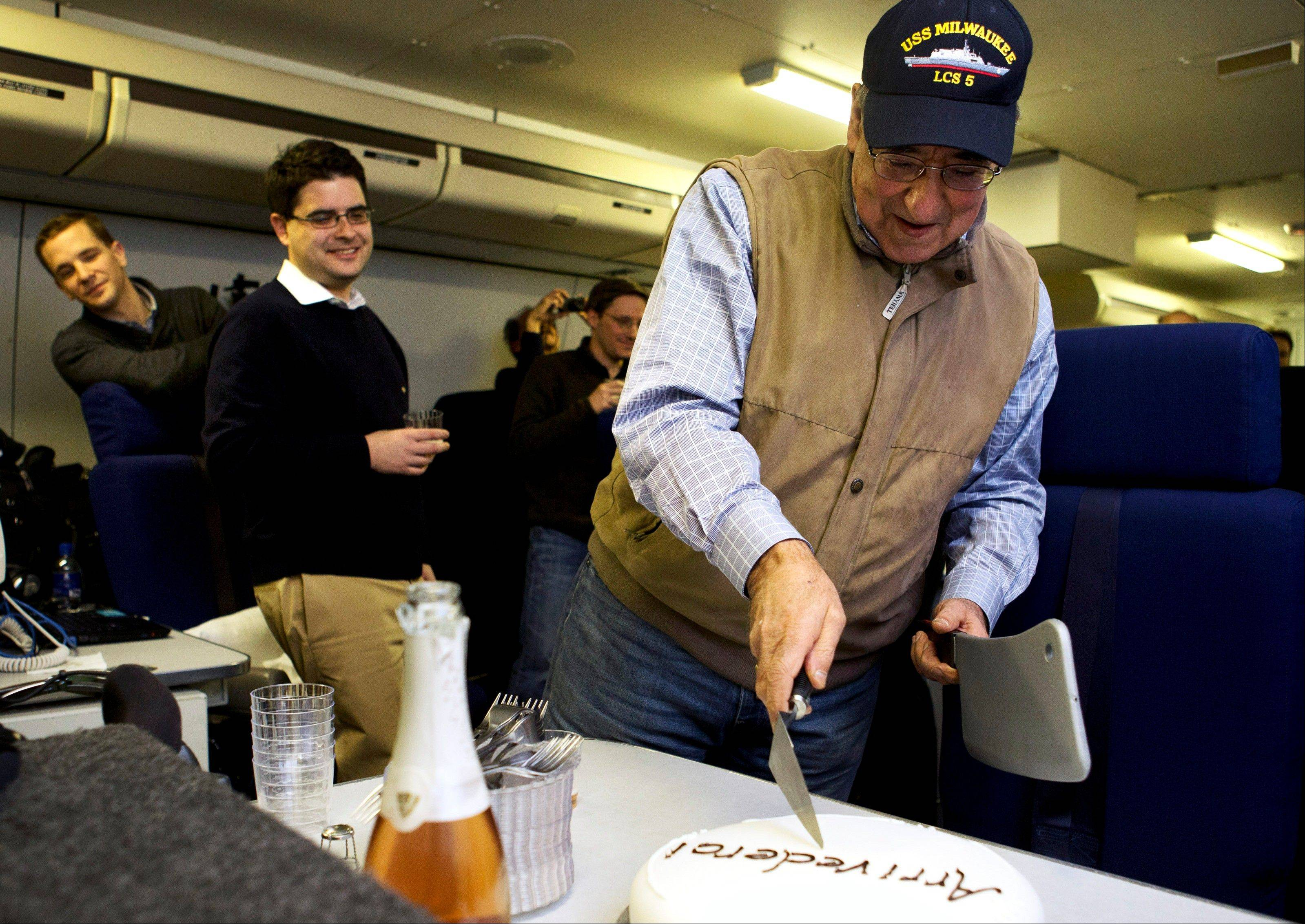 "The traveling staff on board the E-4B surprise U.S. Defense Secretary Leon Panetta with a cake that says ""arrivederci,"" in a celebration in honor of the last leg of his final overseas trip as secretary, en route to Washington on Saturday."