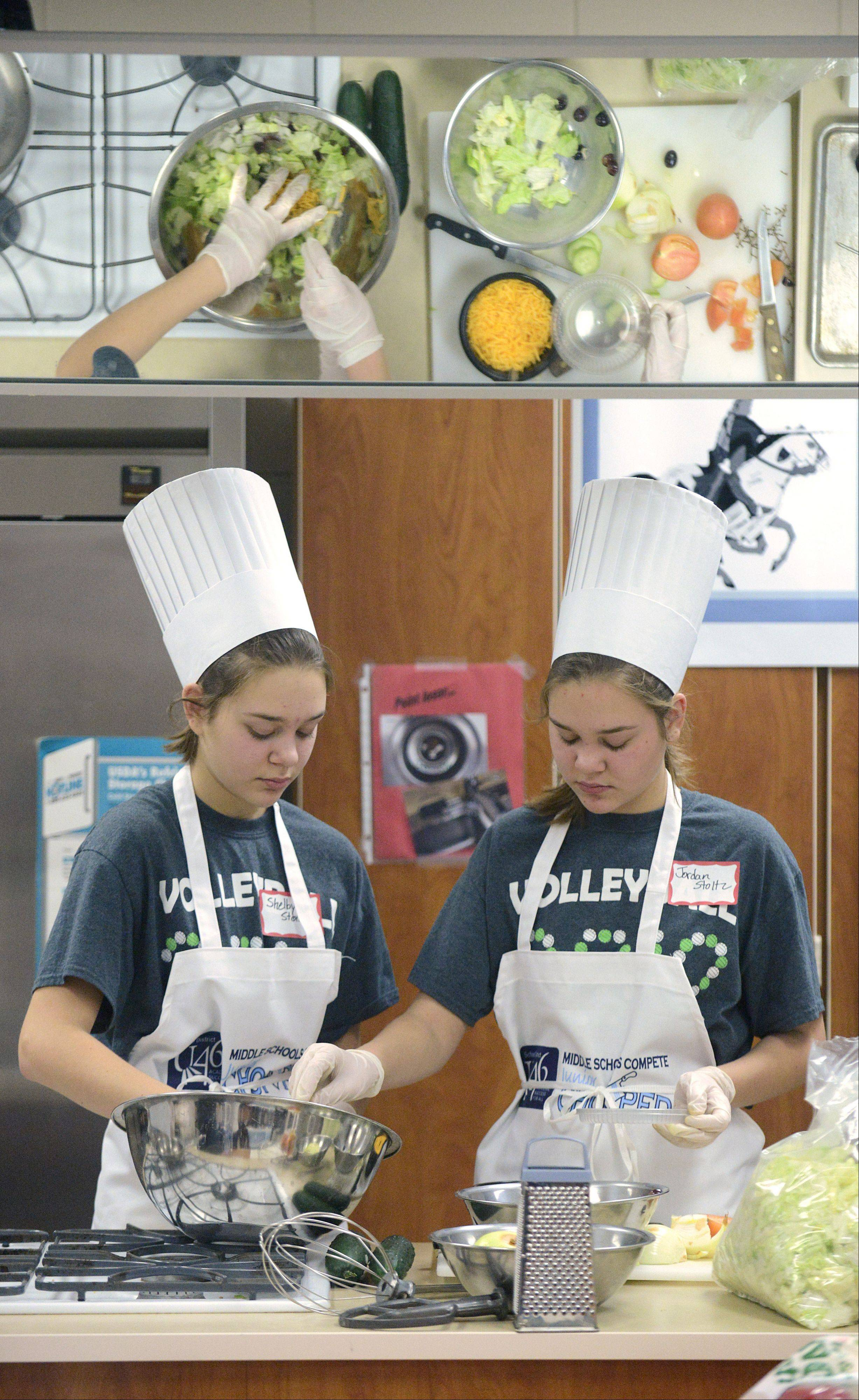 Twin sisters Shelby and Jordan Stolz, 13, of Elgin work on their team's lunch dish in the final round of the Junior Chopped competition Saturday. The girls, along with teammate Allison Densmore, 13, of Hoffman Estates, were on the Cupcakes team from Larsen Middle School.