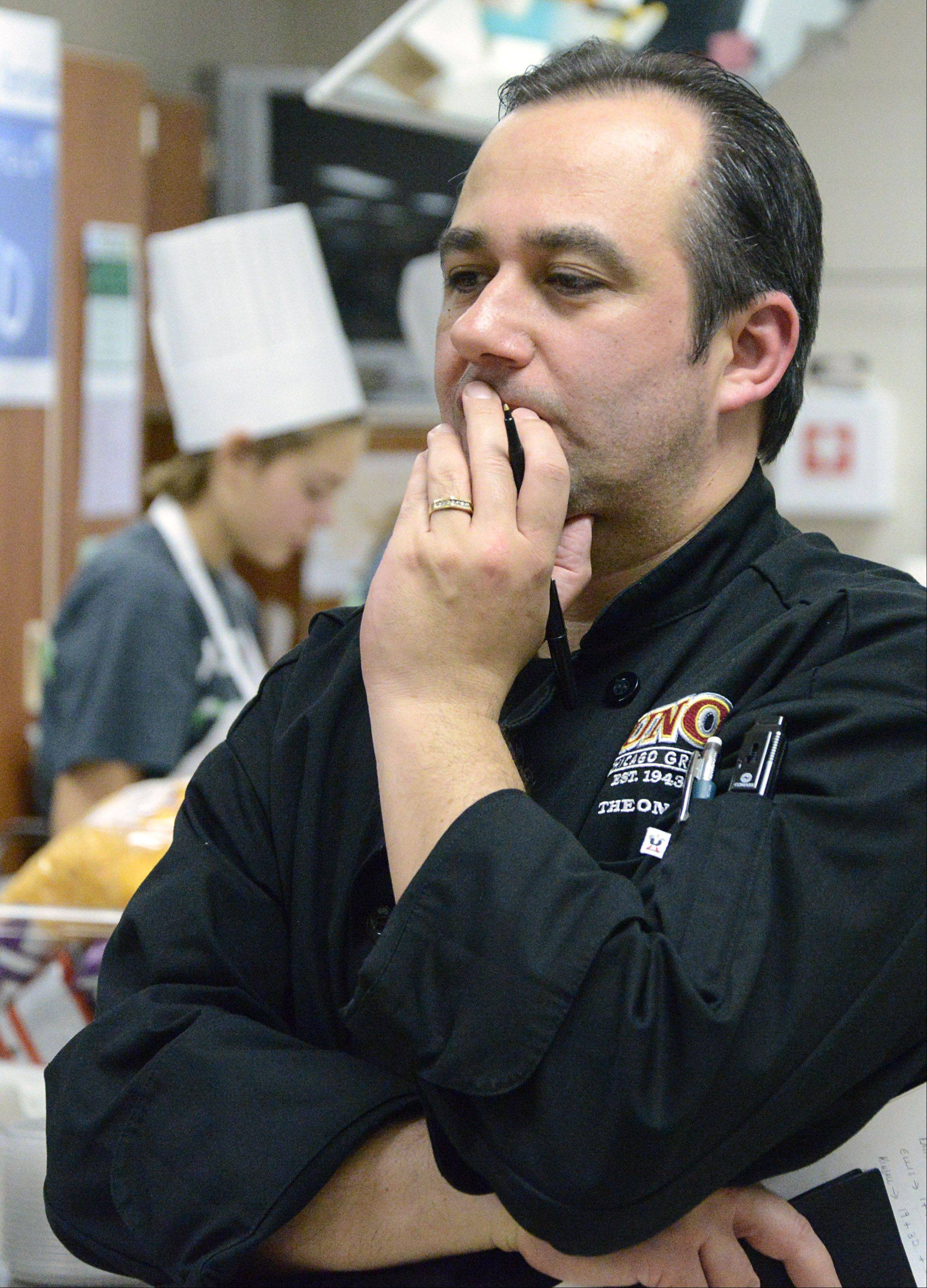 Competition judge Franco Riza Korur, a chef partner with Uno's of Chicago, takes a close look at work of the Swaggy Choppers team from Kimball Middle School during the final round of the Elgin Area School District U-46 Junior Chopped competition Saturday at South Elgin High School.