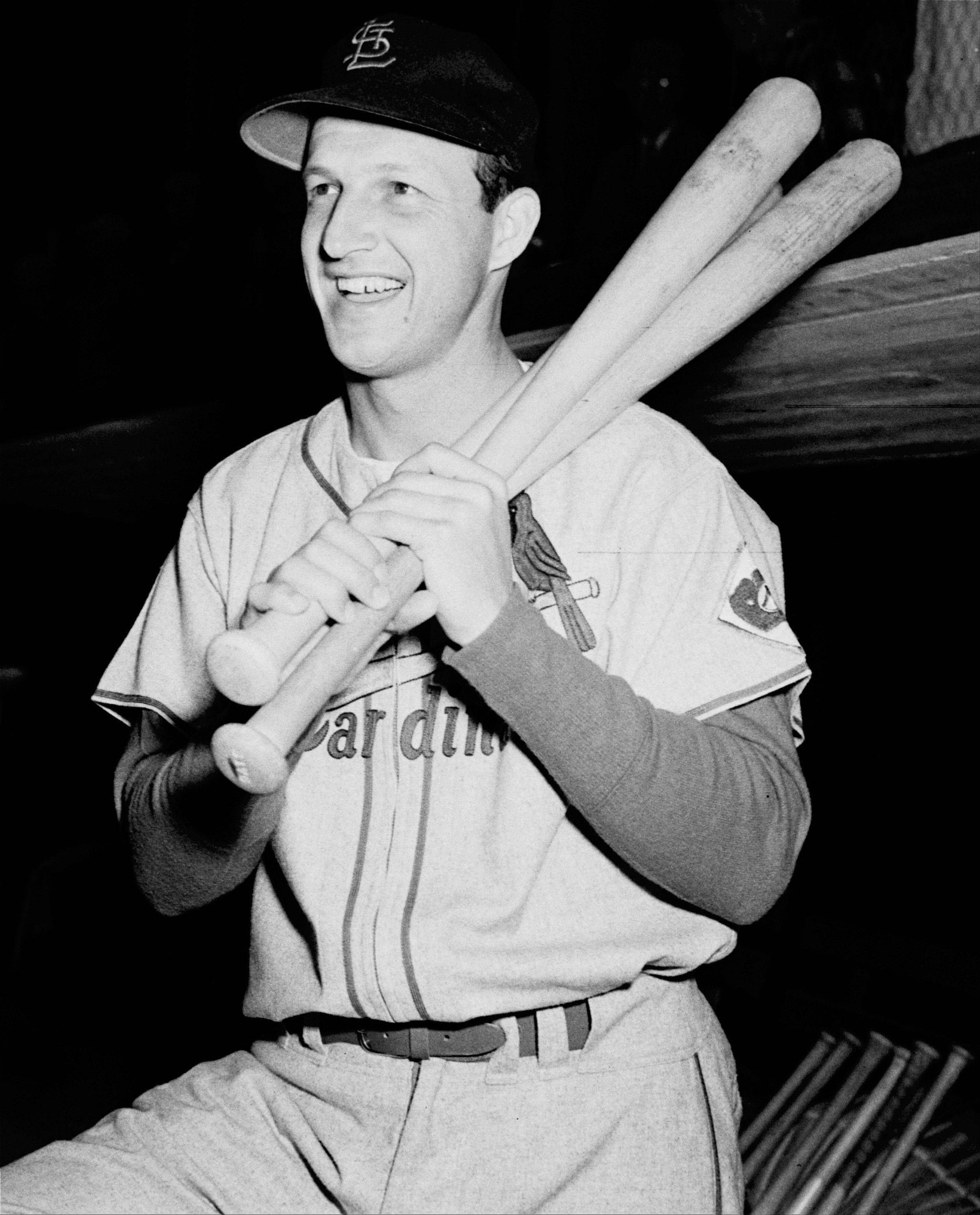 St. Loius Cardinal Stan Musial poses with his bats on his shoulder as he put on his uniform for the first time at spring training baseball in St. Petersburg, Fla.