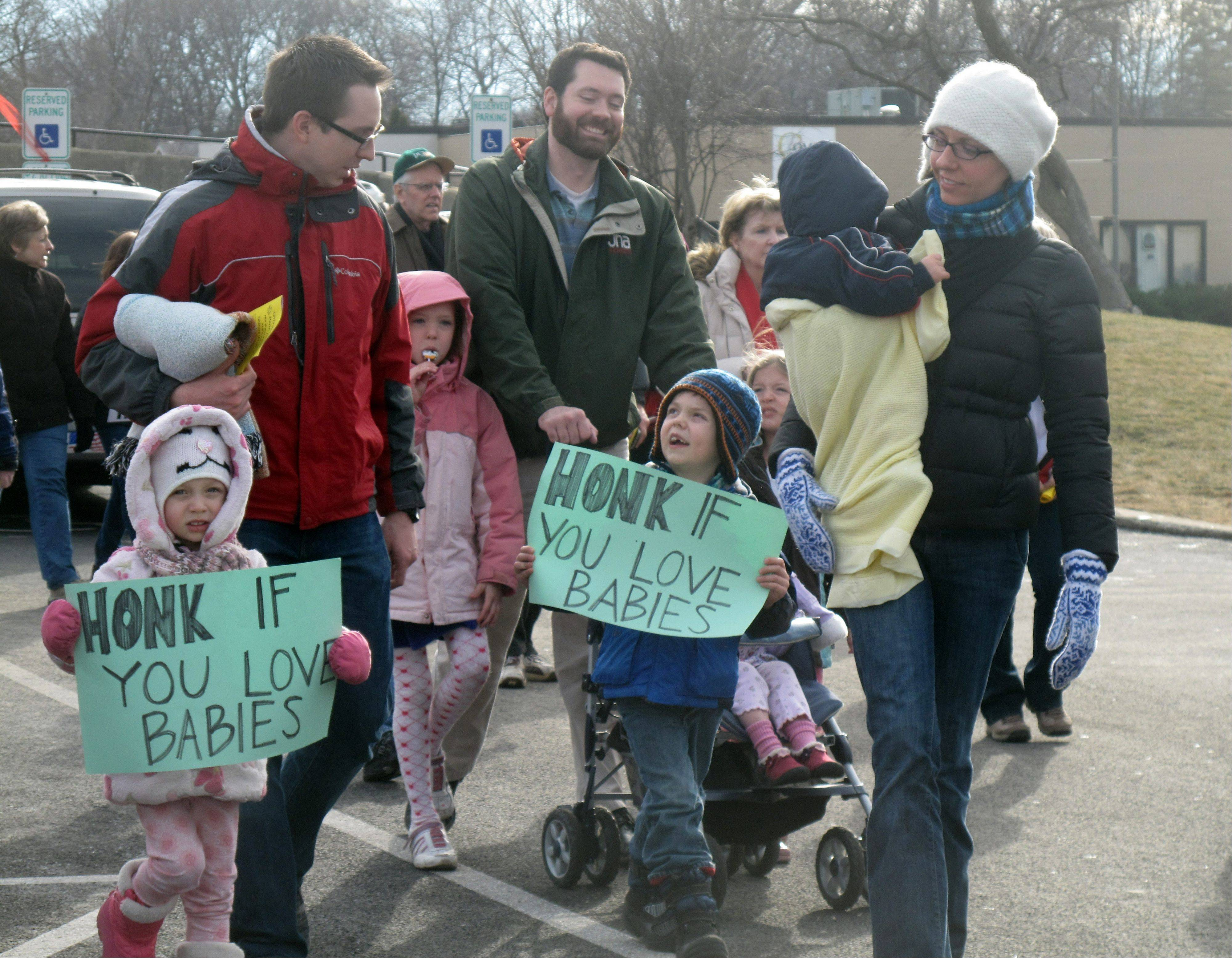 "Lucy Fisher, 3, and James Fisher, 5, carry ""Honk if you love babies"" signs Saturday in Palatine as they participate in Northwest Families for Life's first ""March for Life"" with their parents, Stan and Kelly Fisher of Wheaton."