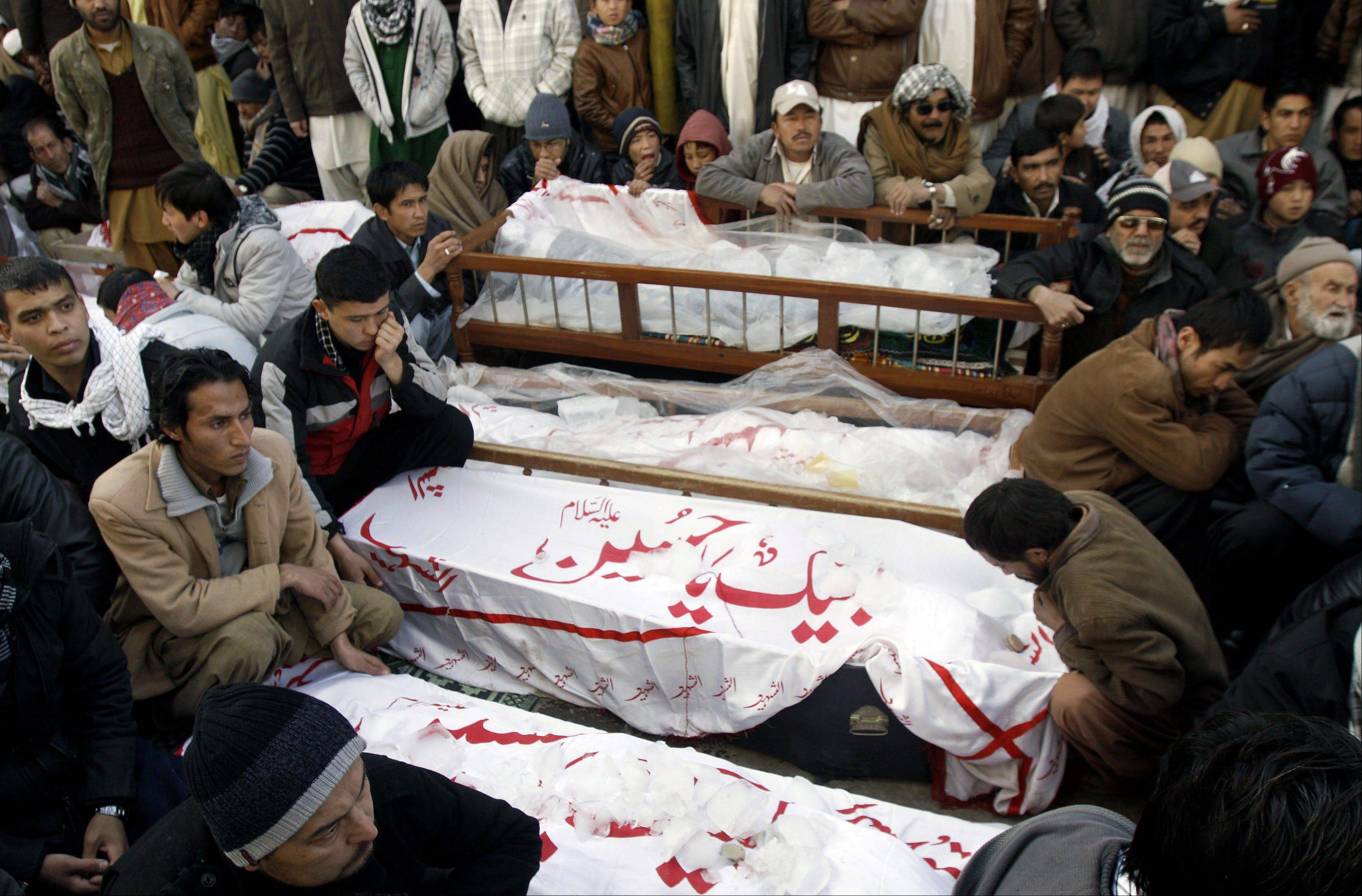 Pakistani Shiite Muslims on Jan. 12 sit next to the bodies of their relatives, who were killed in Jan. 10 bombings in Quetta.