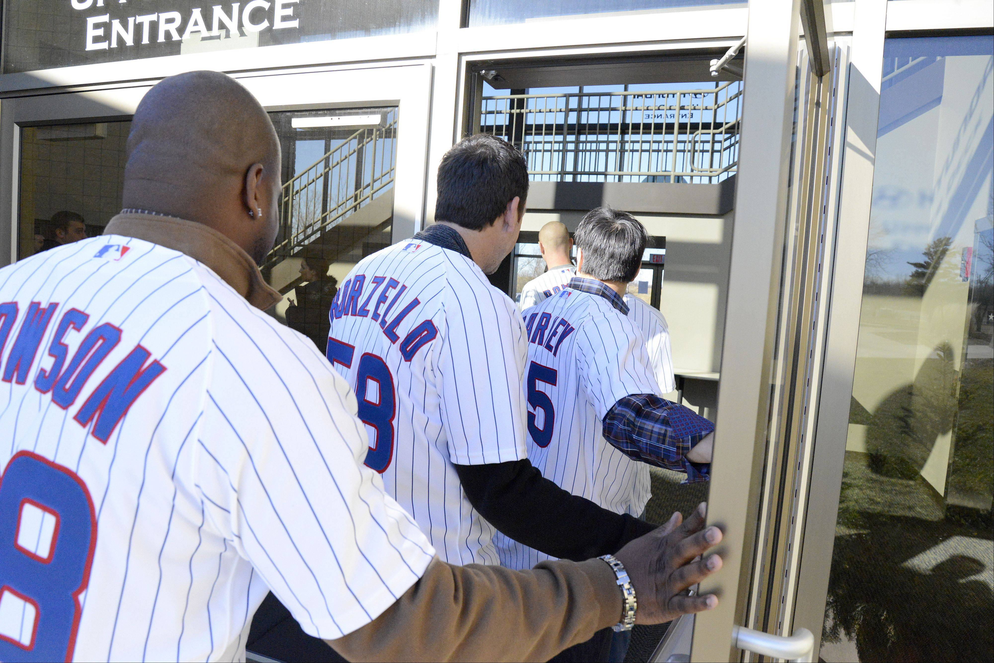 Chicago Cubs hitting coach James Rowson, staff assistant Mike Borzello and second baseman and 2012 Gold Glove winner Darwin Barney enter the Kane County Cougars office for a quick visit in Geneva Jan. 17. Players, coaches and staff of the Chicago Cubs Cubs On the Move 2013 Caravan Tour came by for about 30 minutes after meeting with children at an Oswego school.