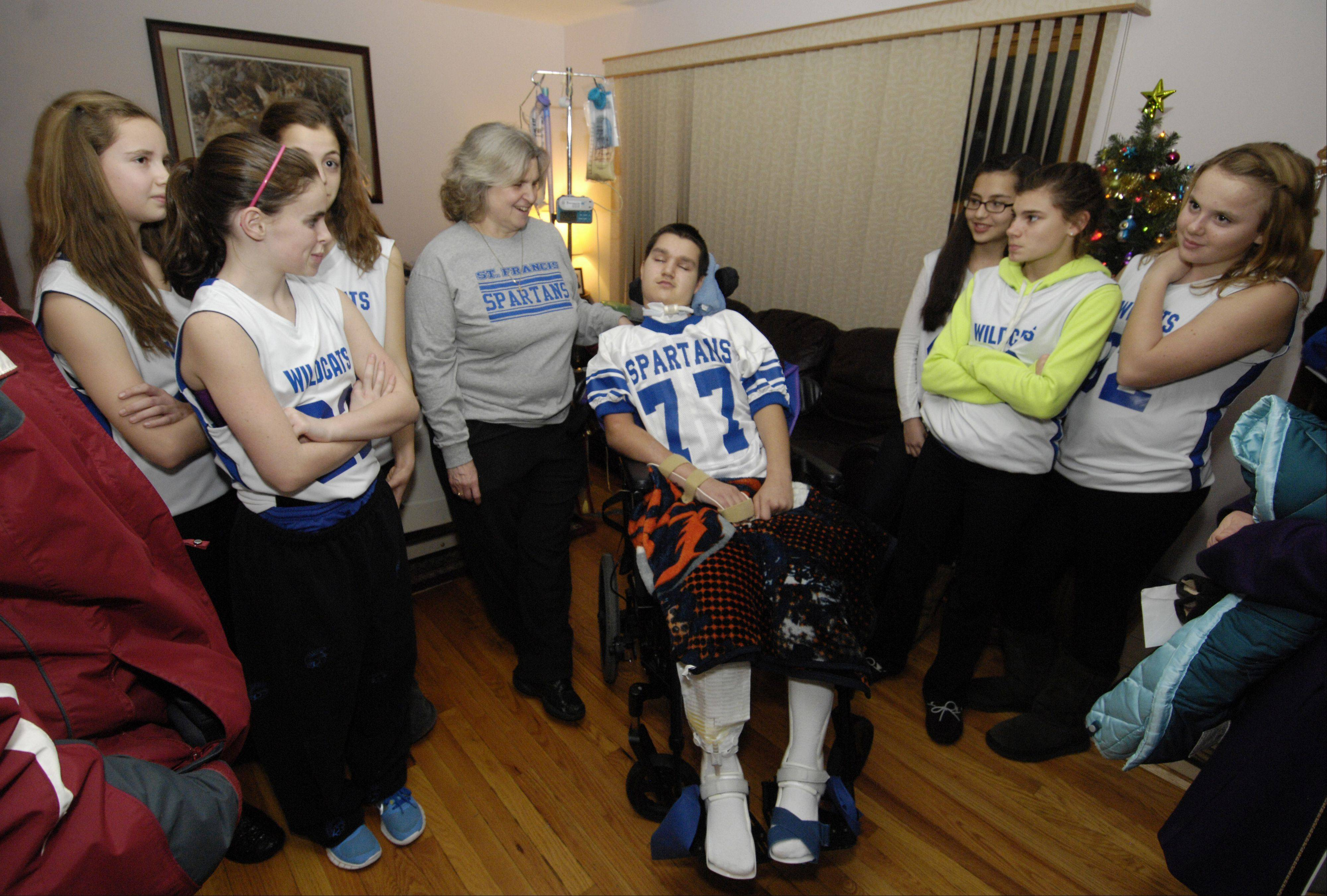 Alex Novak, 15, of West Chicago, receives a donation from members of the St. John the Baptist School girls basketball team.