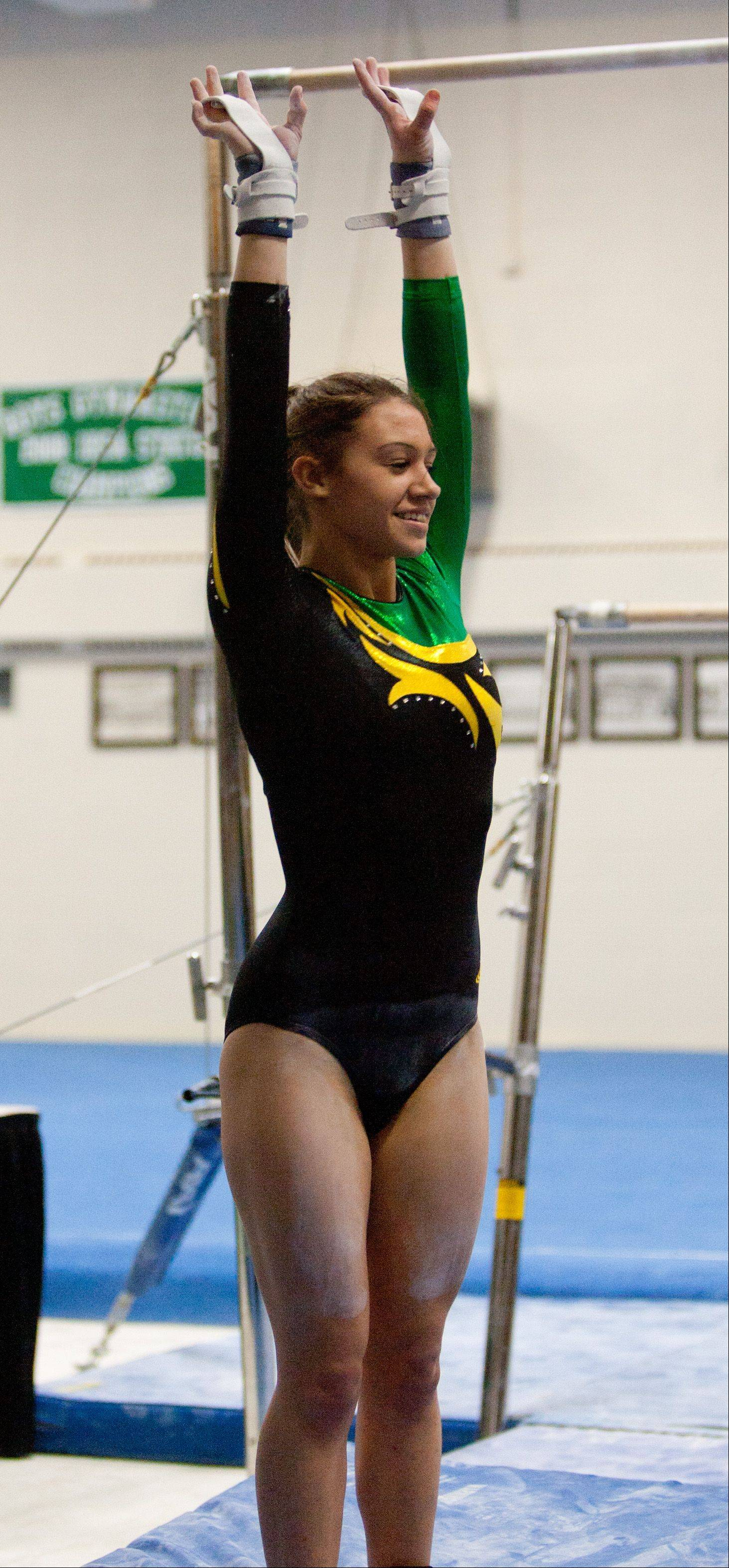 Waubonsie Valley High School's Jessica Malon finishes her uneven parallel bar during the York Girls' Gymnastics Invite.